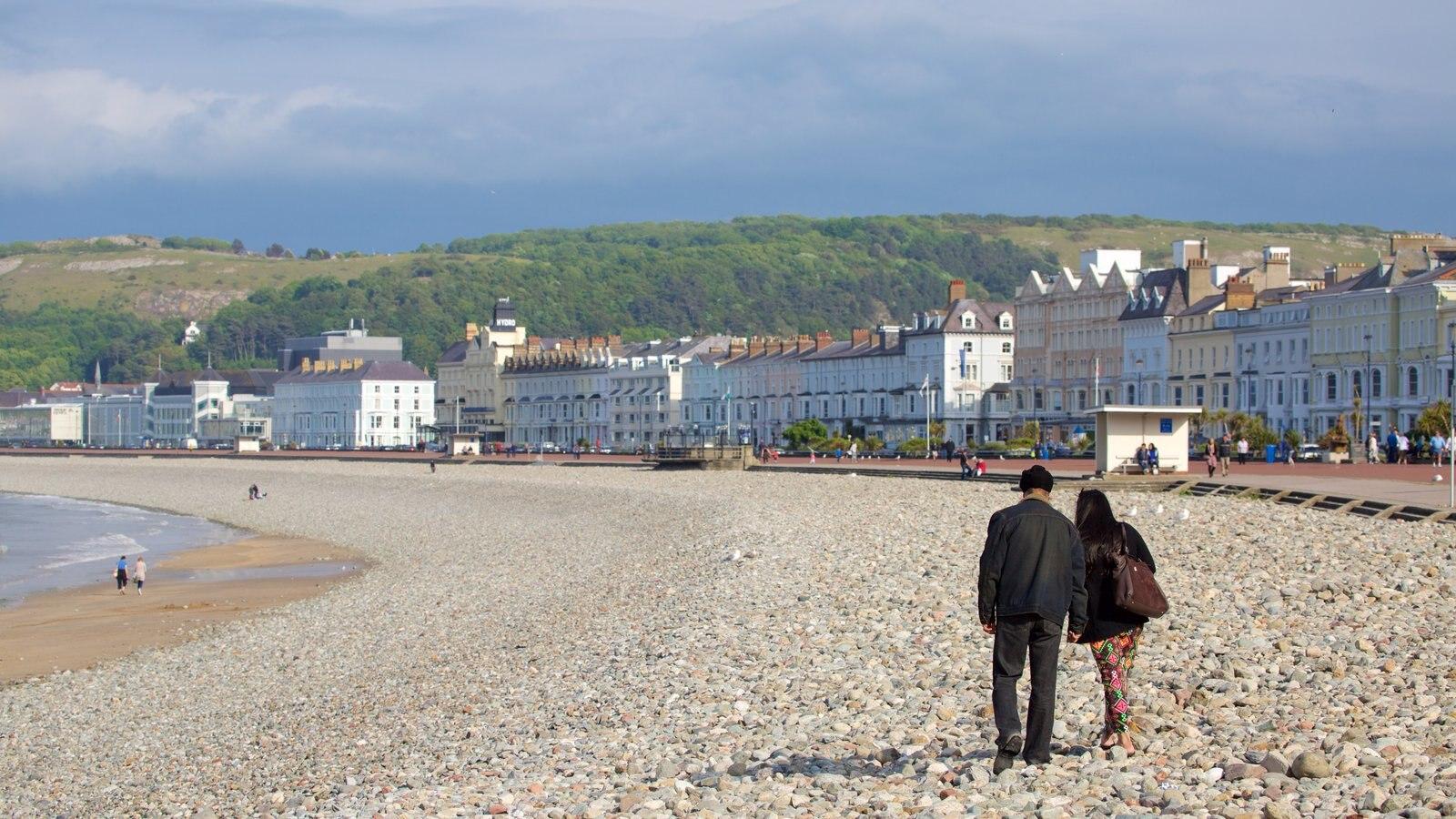 Llandudno mostrando una playa de guijarros y también una pareja