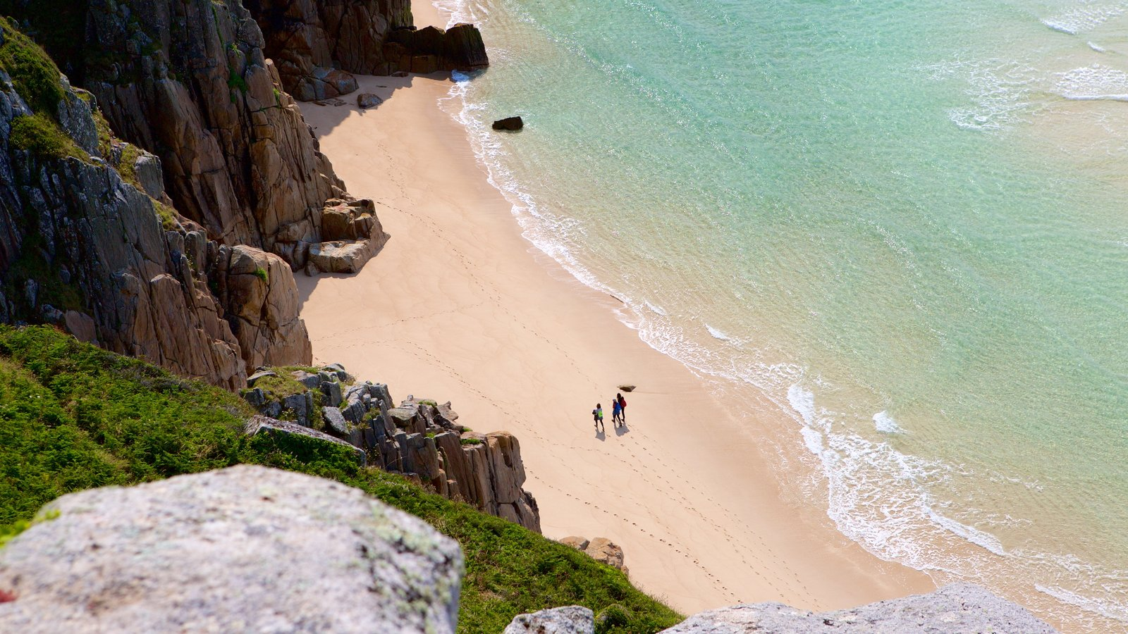 Porthcurno Beach which includes a sandy beach and rugged coastline