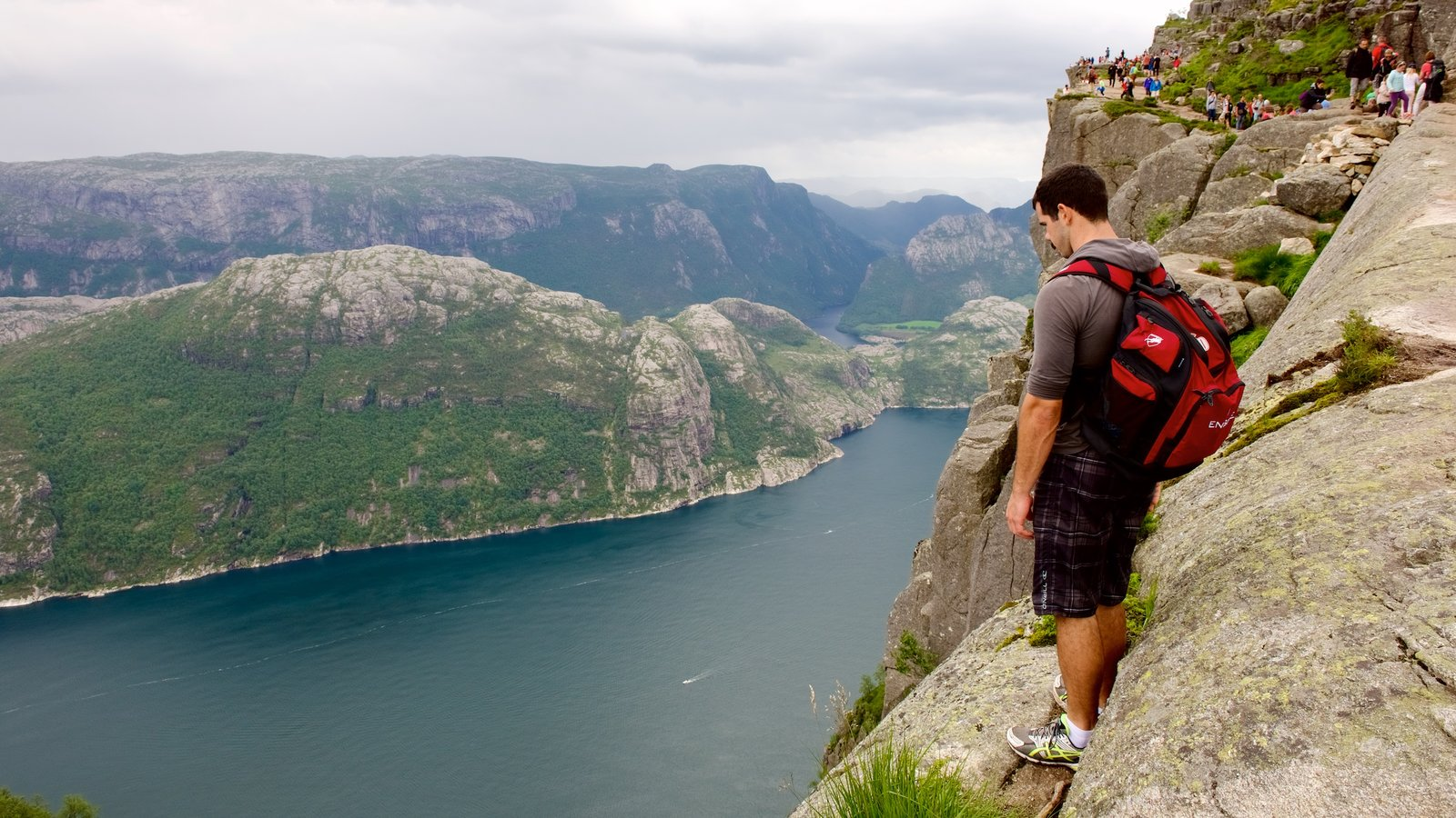 Preikestolen featuring mountains and a lake or waterhole as well as an individual male