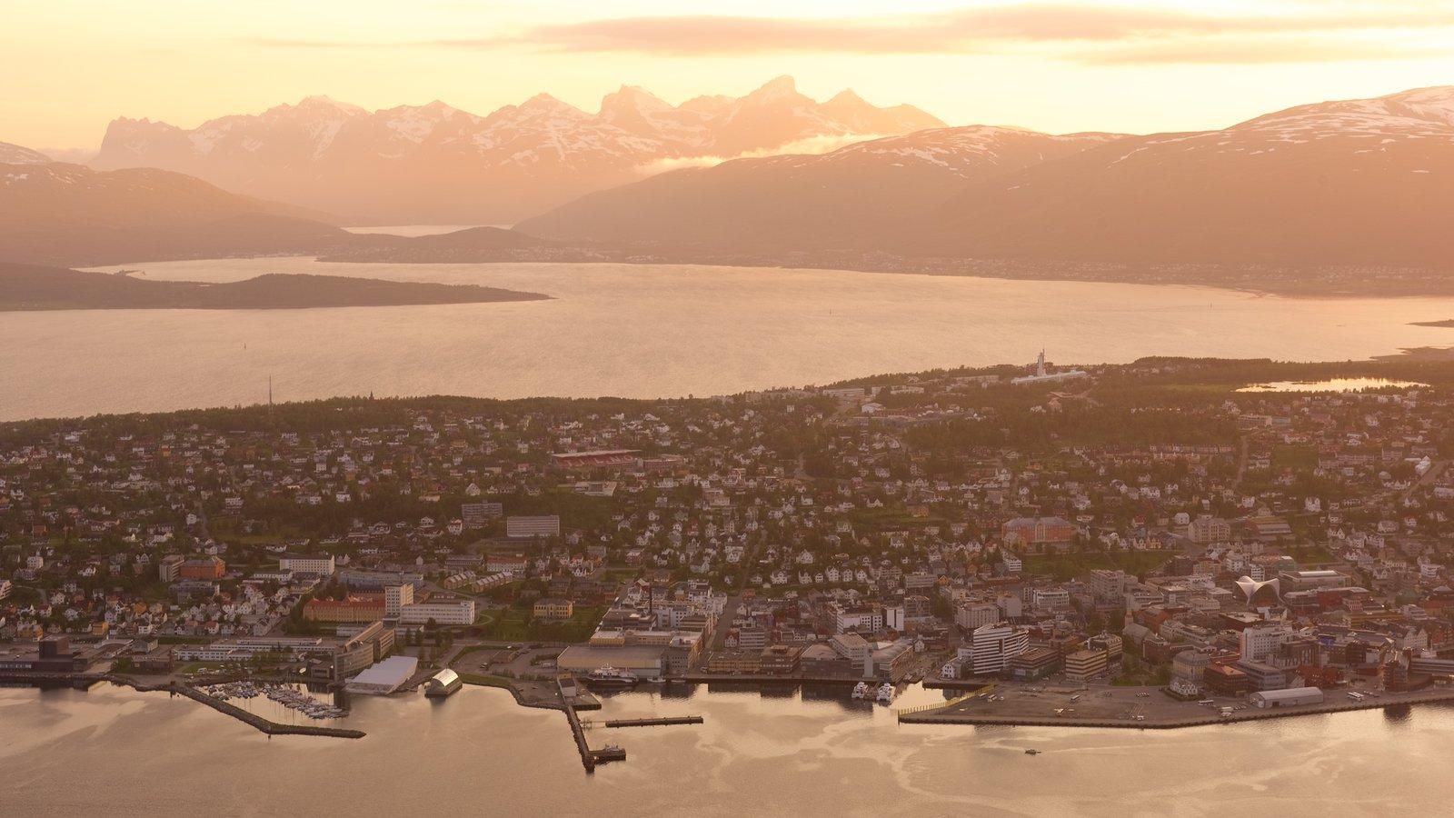 Tromso caracterizando um lago ou charco, um pôr do sol e uma cidade pequena ou vila