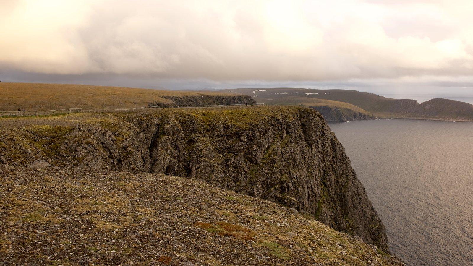 Península Knivskjellodden que incluye una puesta de sol, un lago o abrevadero y montañas