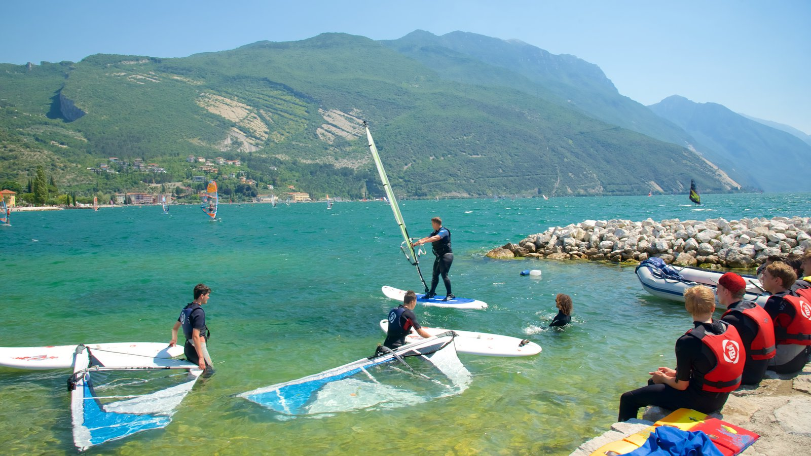 Nago-Torbole which includes kite surfing and rugged coastline as well as a small group of people