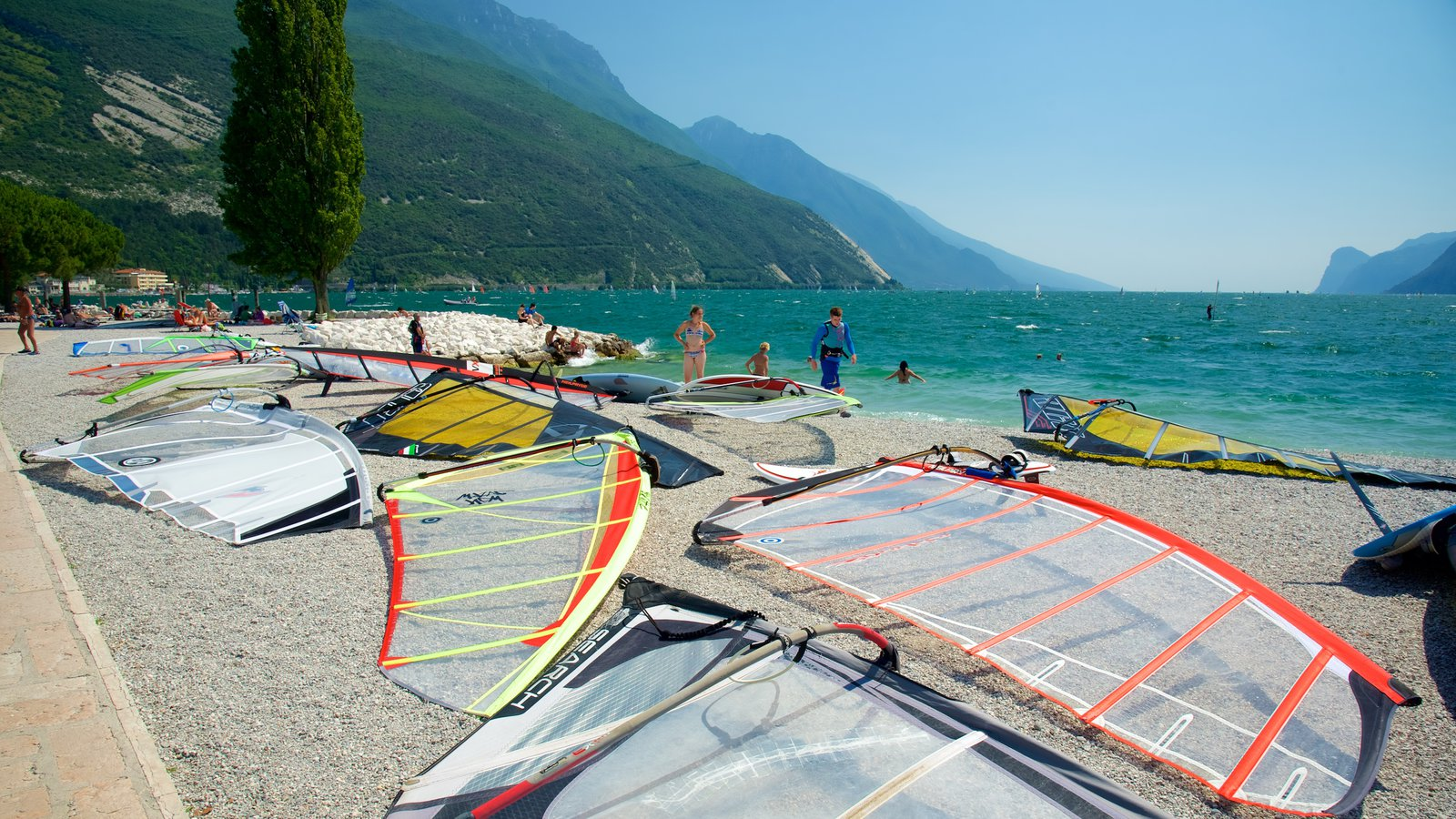 Nago-Torbole featuring a pebble beach and windsurfing as well as a large group of people