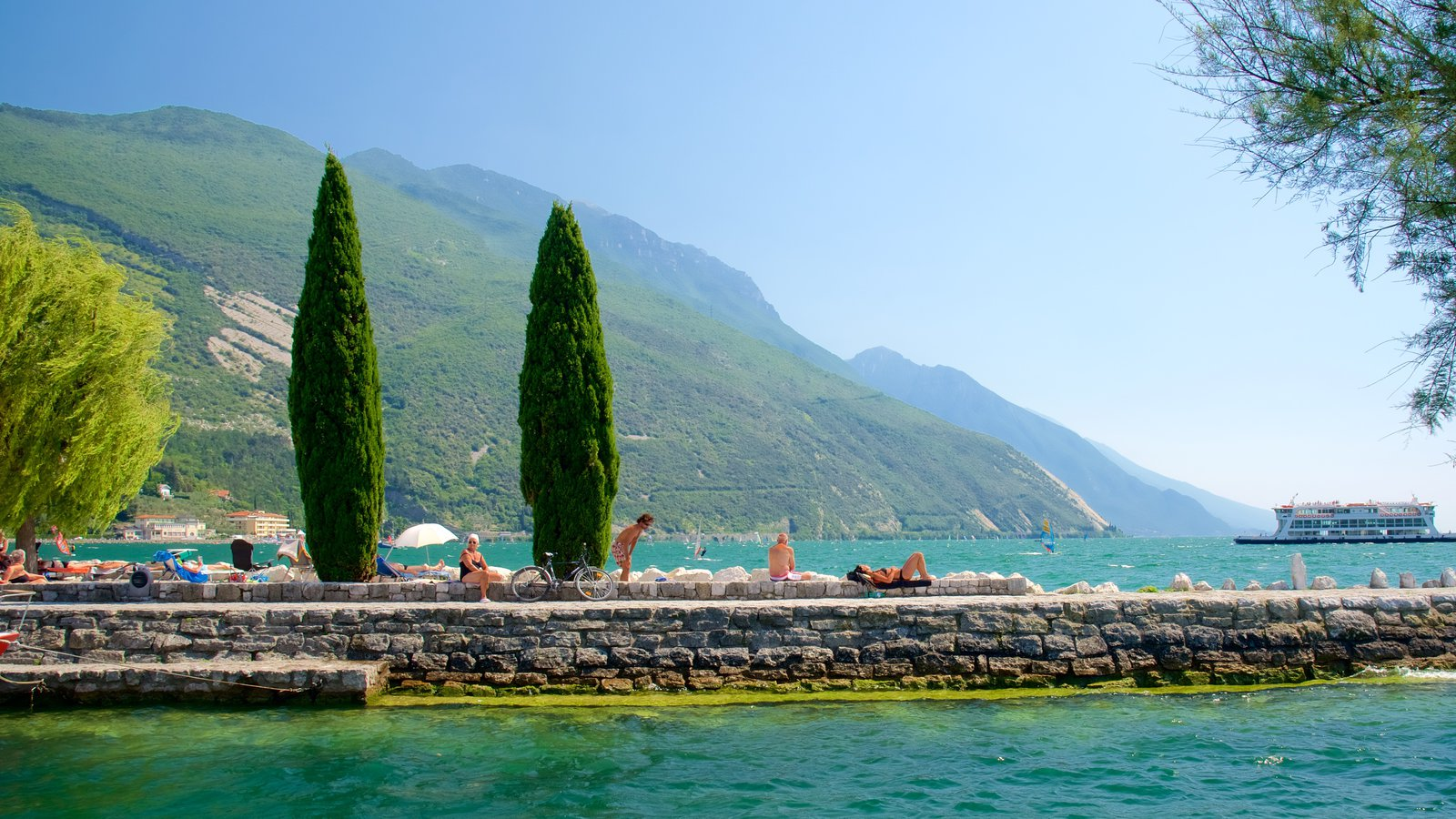 Nago-Torbole showing boating and general coastal views as well as a small group of people