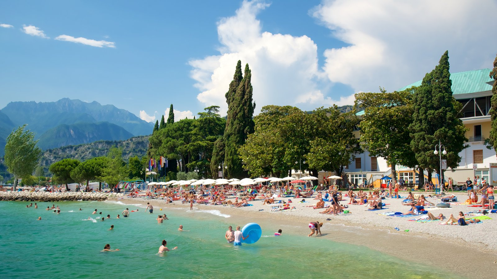 Nago-Torbole which includes a coastal town, a beach and swimming