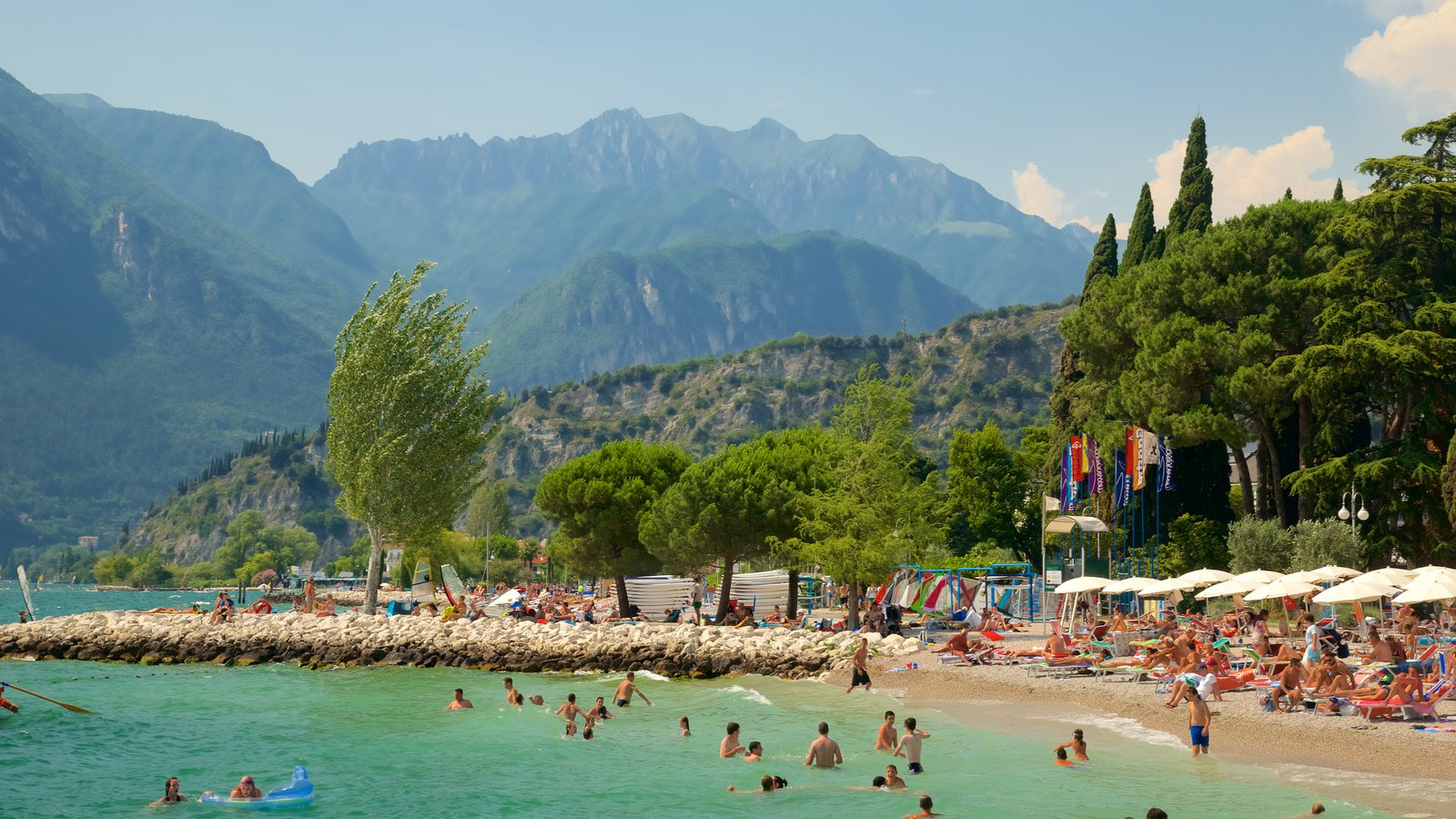 Nago-Torbole showing a beach, a coastal town and mountains
