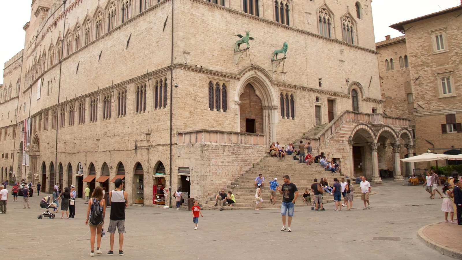 Palazzo dei Priori which includes heritage architecture and a square or plaza as well as a large group of people