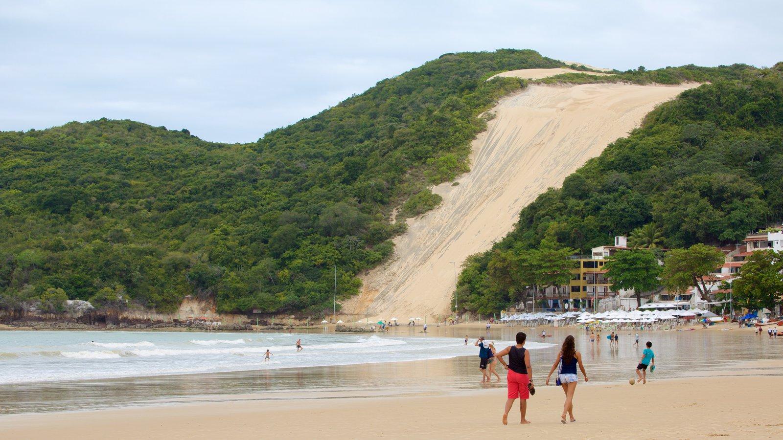 Praia de Ponta Negra que inclui uma cidade litorânea e uma praia assim como um pequeno grupo de pessoas