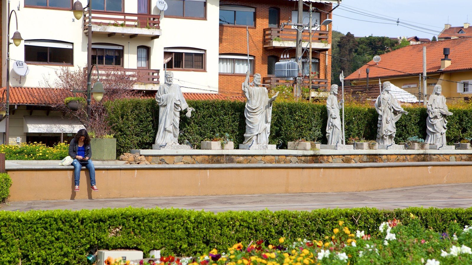 Paróquia de São Pedro Apóstolo mostrando aspectos religiosos e uma estátua ou escultura assim como uma mulher sozinha