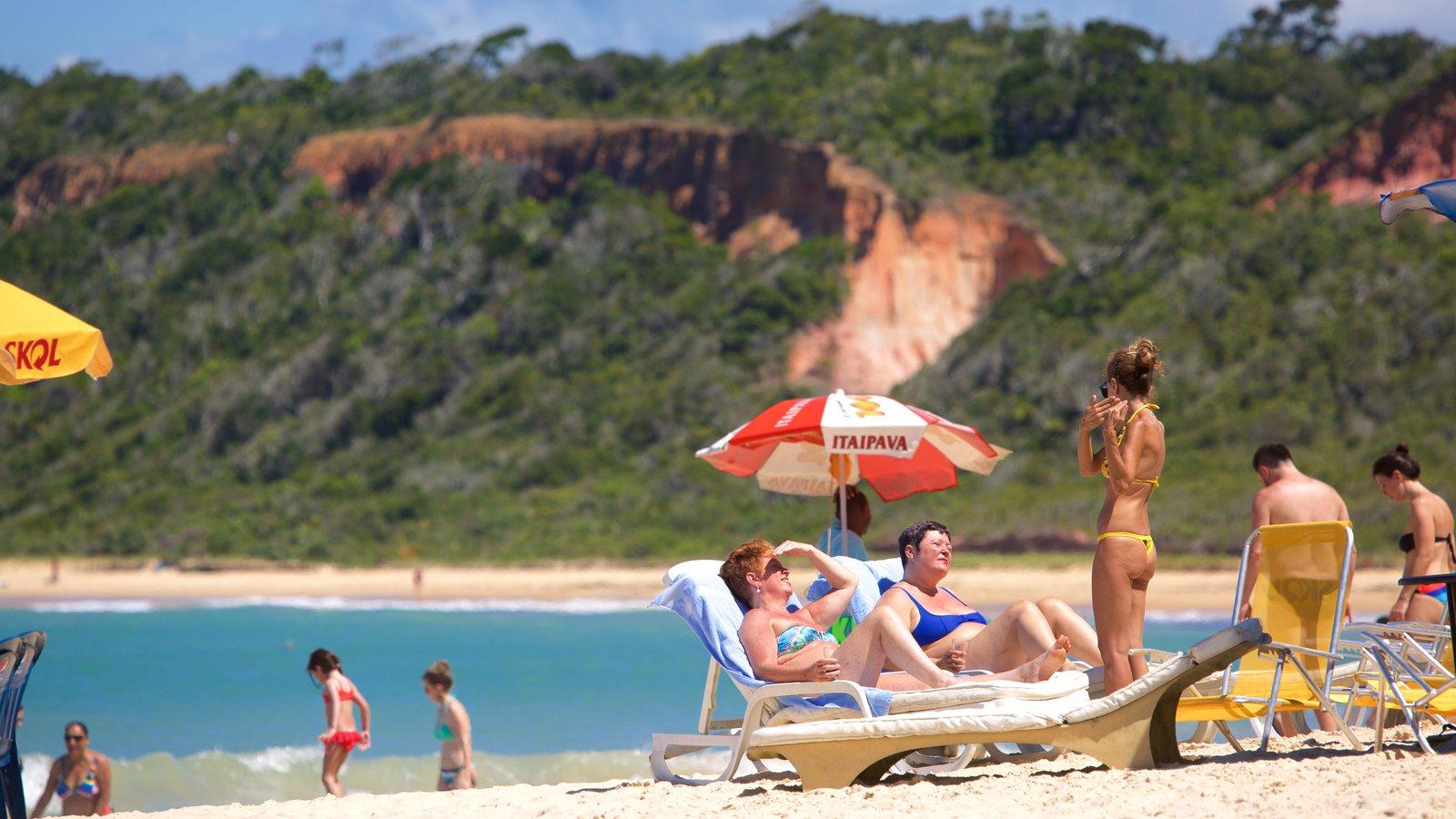 Praia de Pitinga que inclui uma praia de areia e paisagens litorâneas assim como um pequeno grupo de pessoas