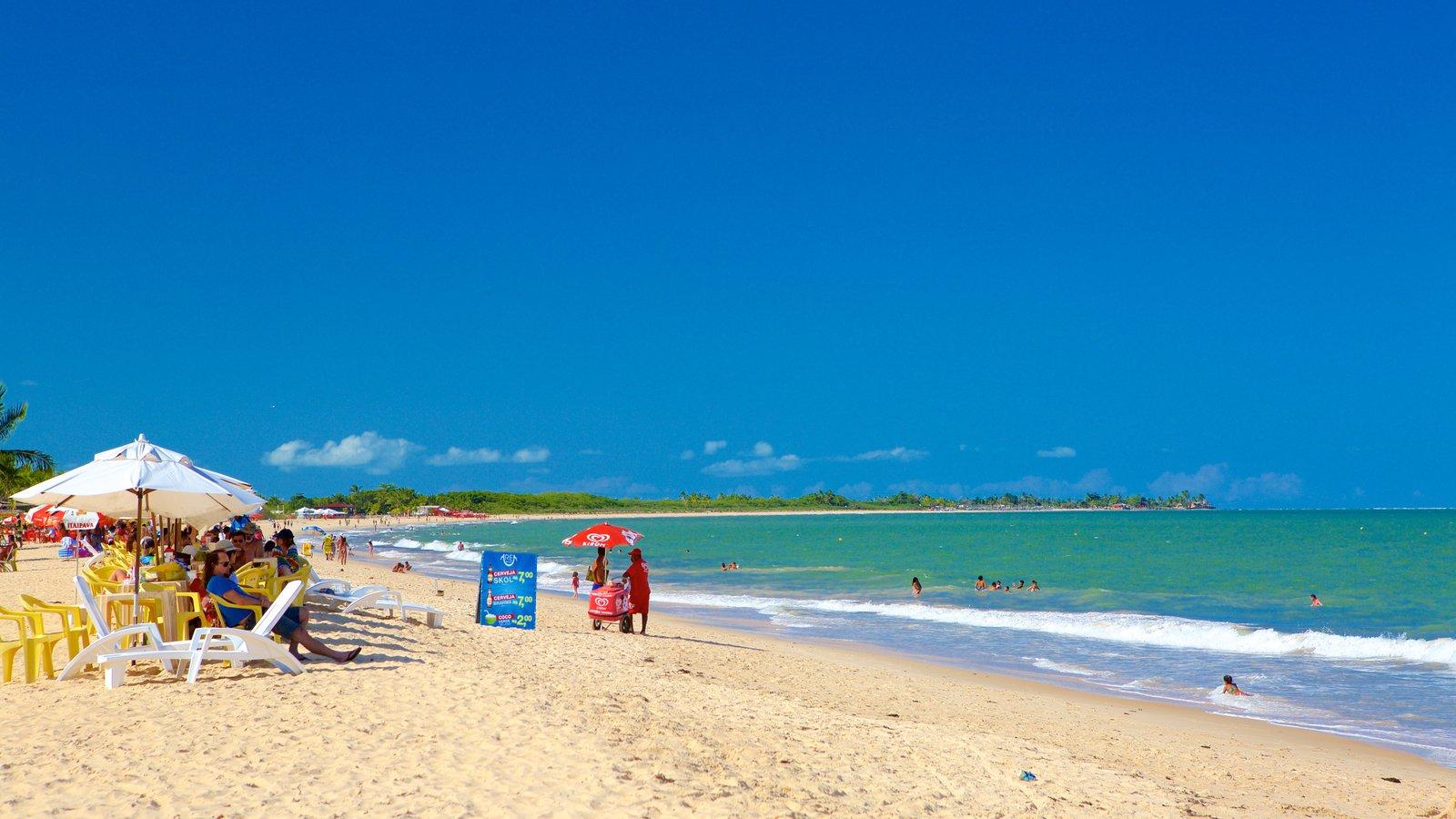Praia de Taperapuã mostrando uma praia de areia e paisagens litorâneas assim como um grande grupo de pessoas
