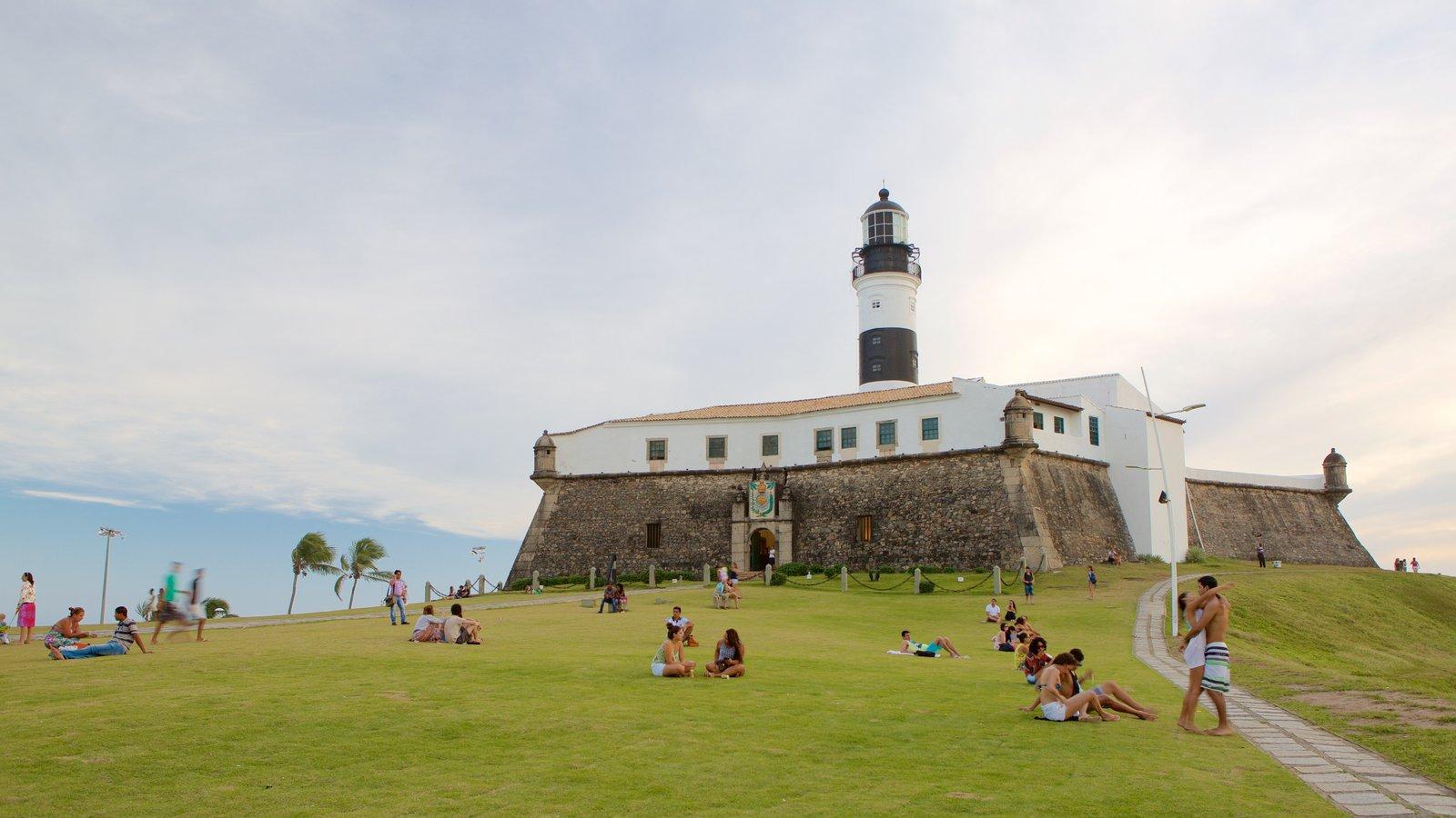 Praia do Farol da Barra mostrando um farol e paisagens litorâneas assim como um grande grupo de pessoas