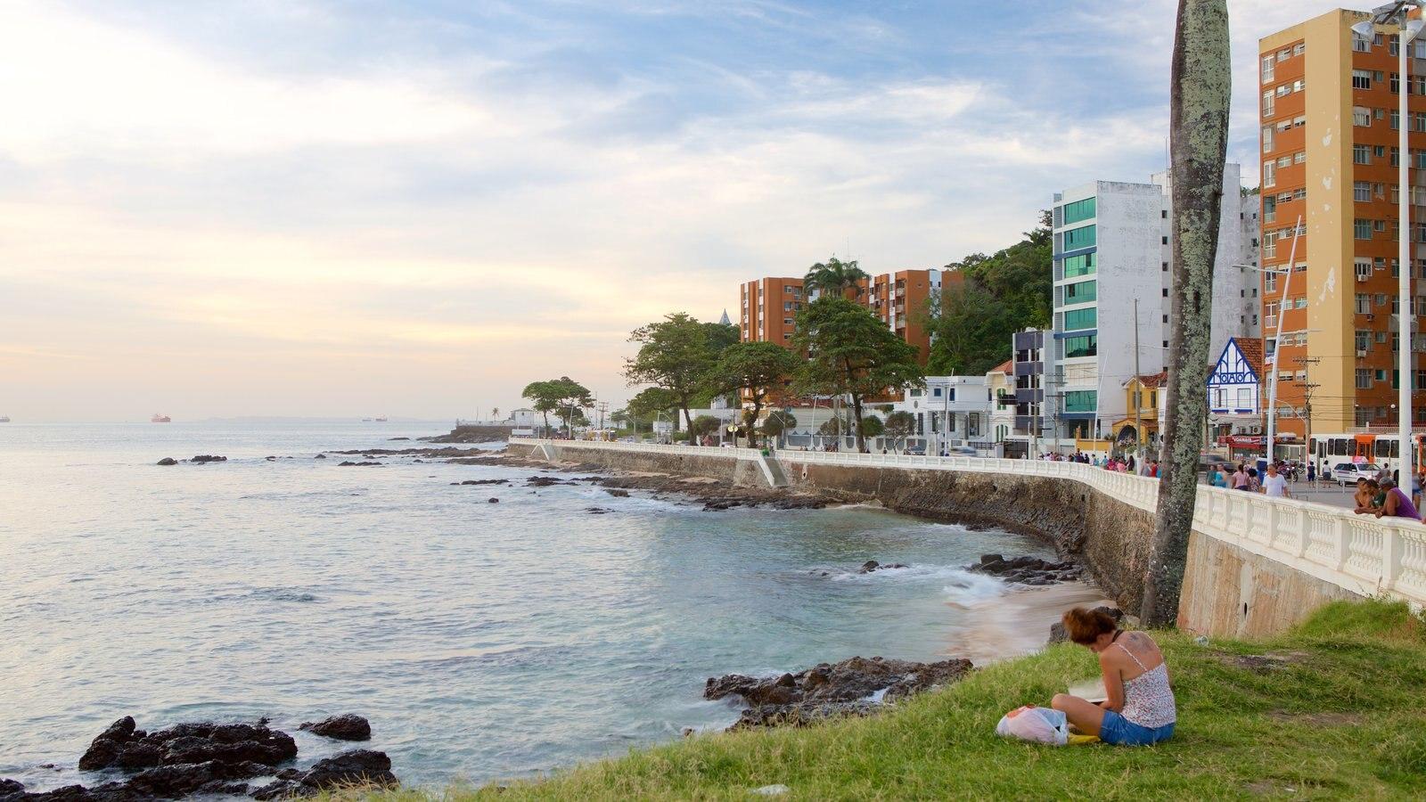 Praia do Farol da Barra que inclui paisagens litorâneas e uma cidade litorânea assim como uma mulher sozinha