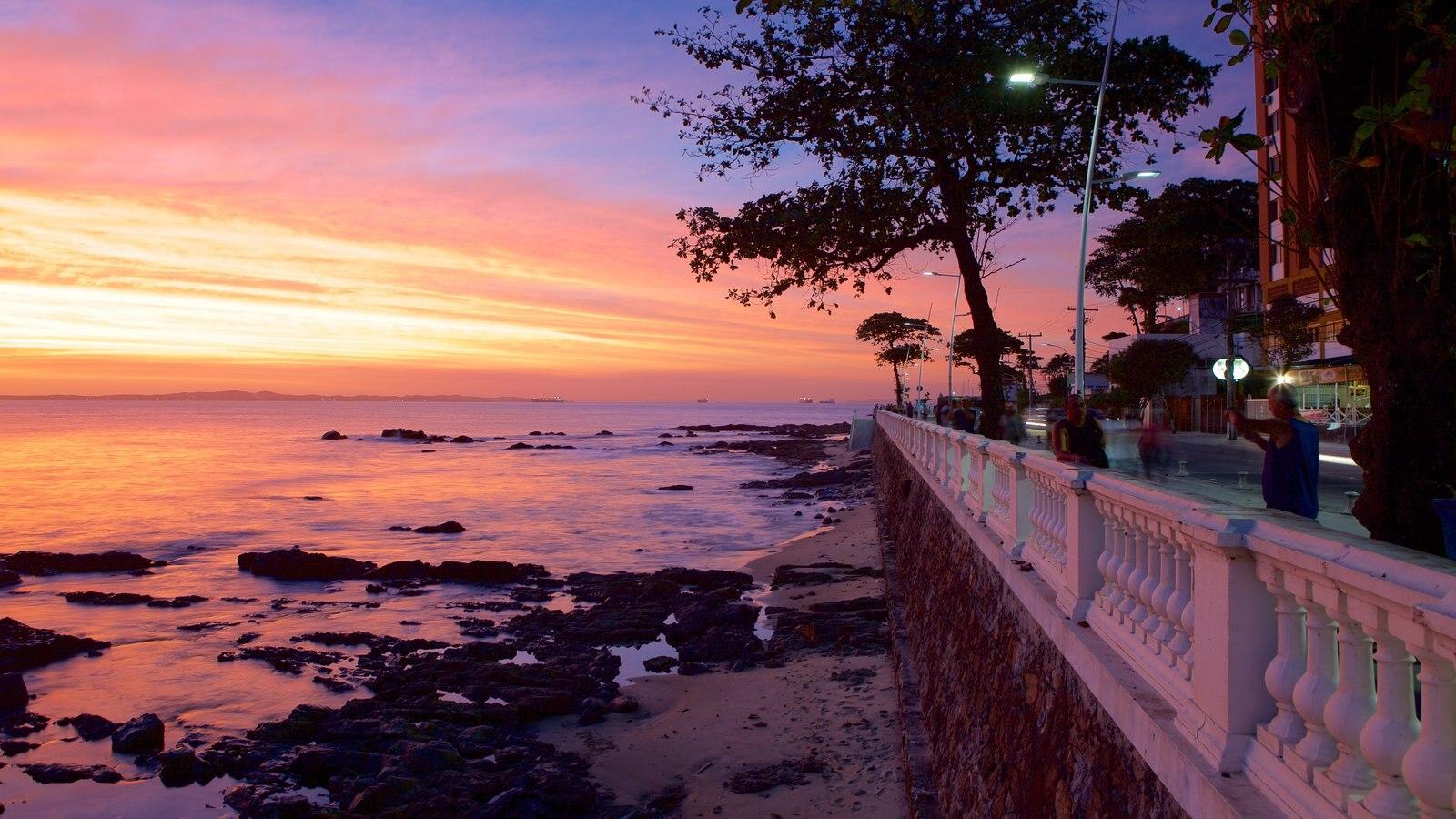 Praia do Farol da Barra caracterizando um pôr do sol, paisagens litorâneas e uma cidade litorânea