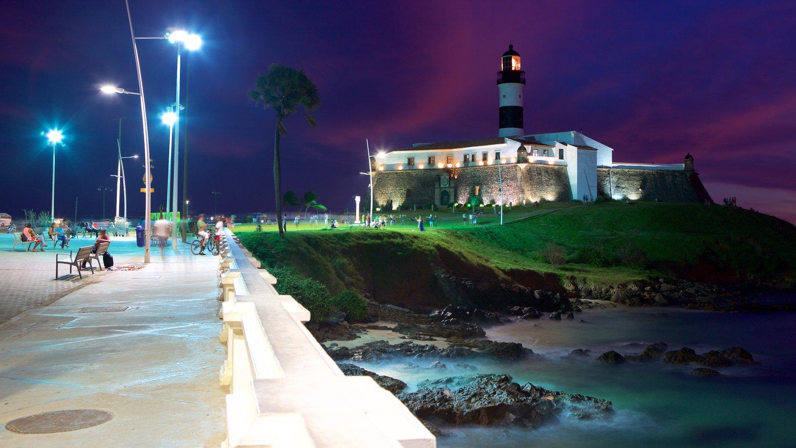 Praia do Farol da Barra que inclui um farol, paisagens litorâneas e cenas noturnas