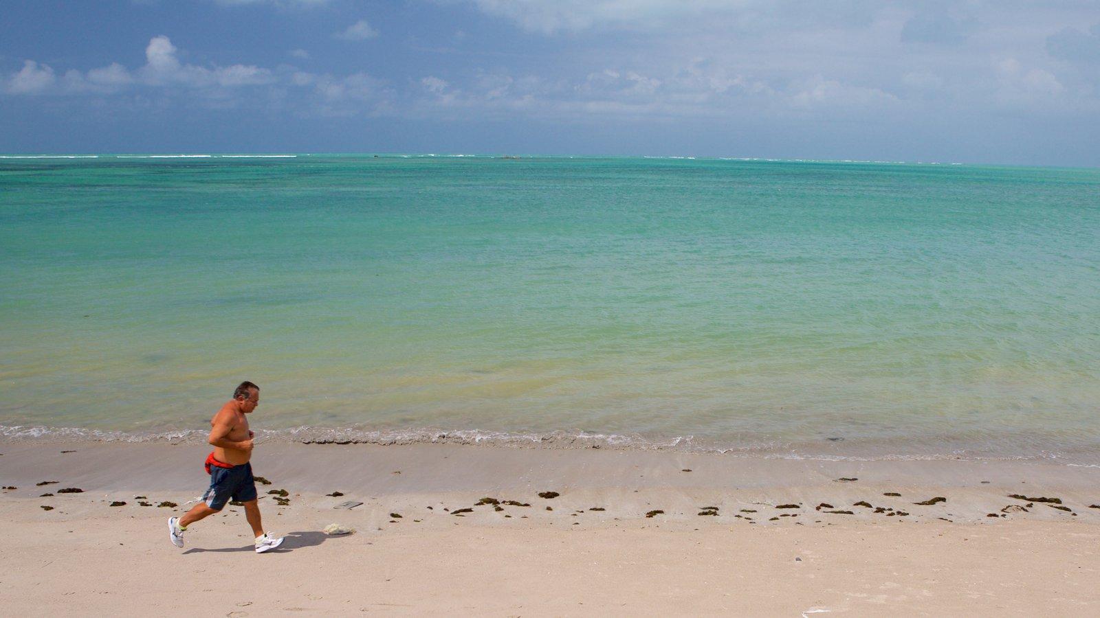 Praia de Ponta Verde mostrando paisagens litorâneas e uma praia de areia assim como um homem sozinho