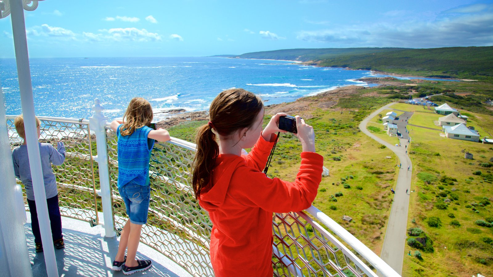 Cape Leeuwin Lighthouse which includes a small town or village and rocky coastline as well as children