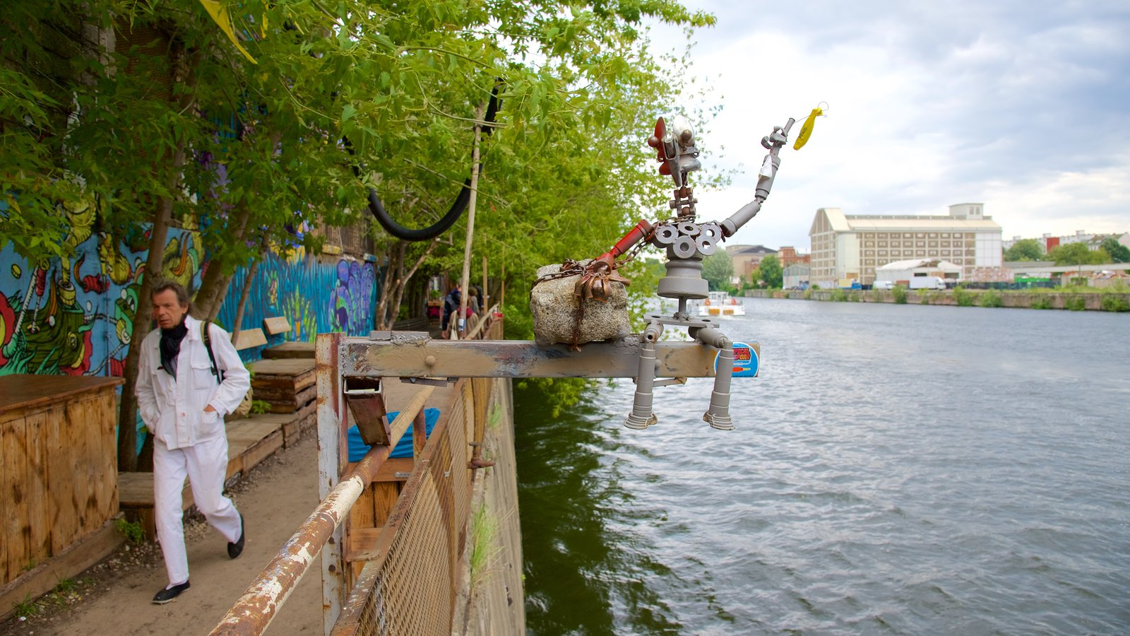 Friedrichshain showing outdoor art and a river or creek as well as an individual male