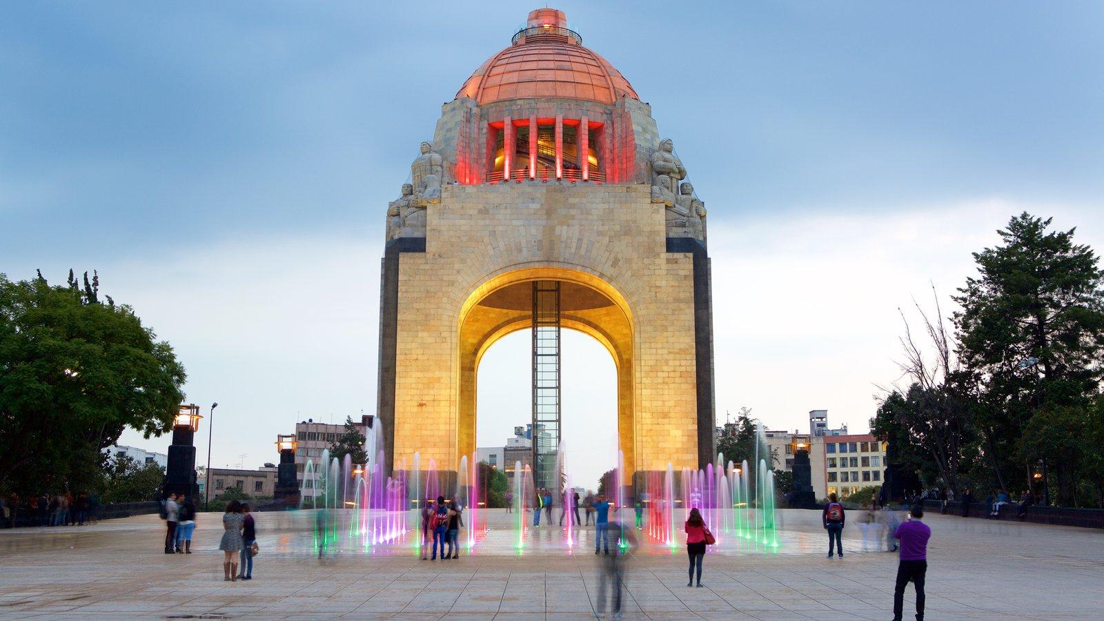 Monumento a la Revolución que incluye una fuente y también un pequeño grupo de personas