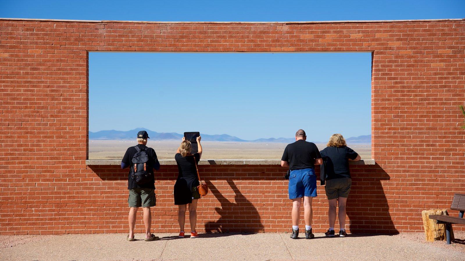 Meteor Crater que inclui cenas tranquilas e paisagens do deserto assim como um pequeno grupo de pessoas