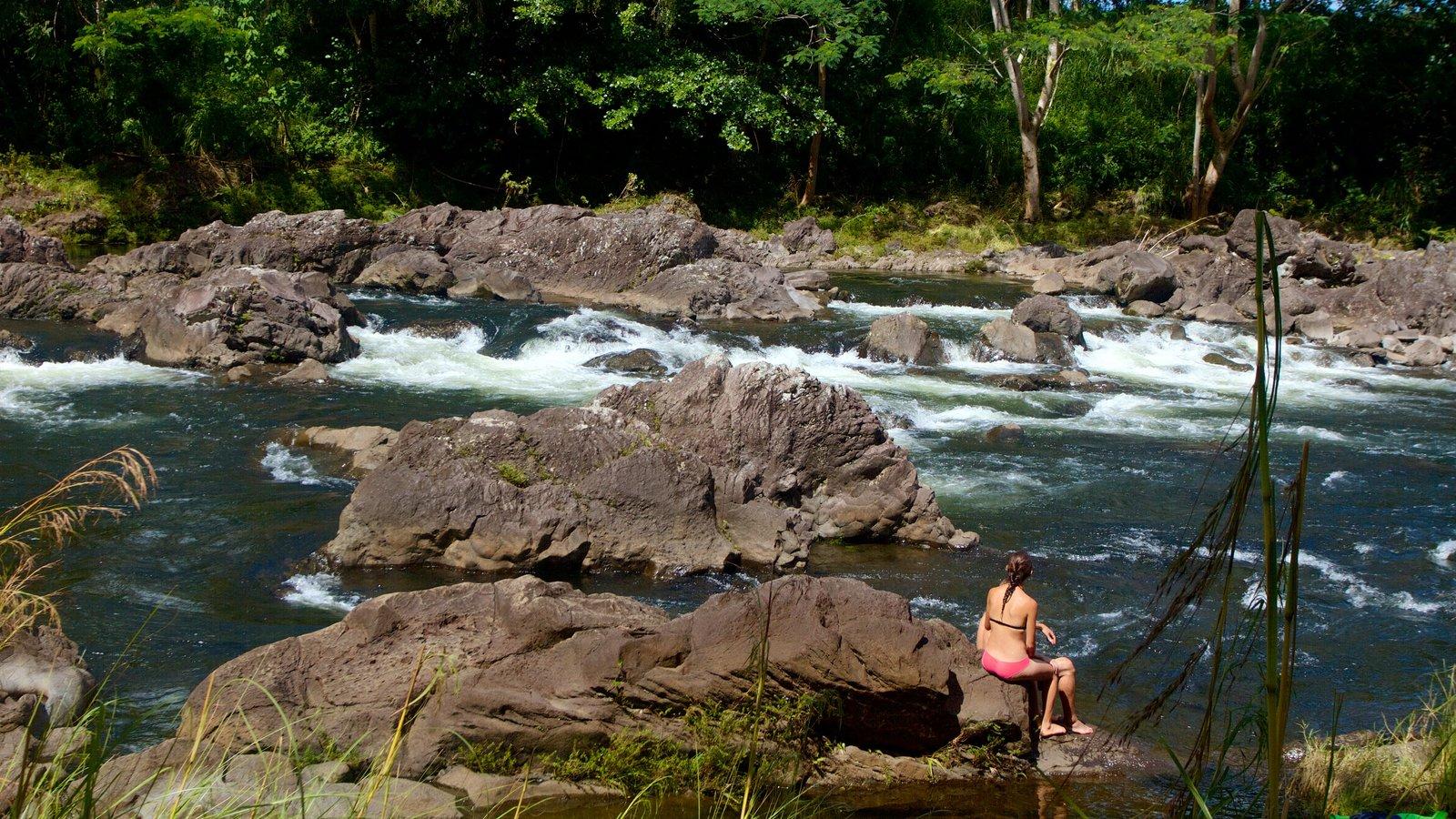 Rainbow Falls caracterizando um rio ou córrego e córrego assim como uma mulher sozinha