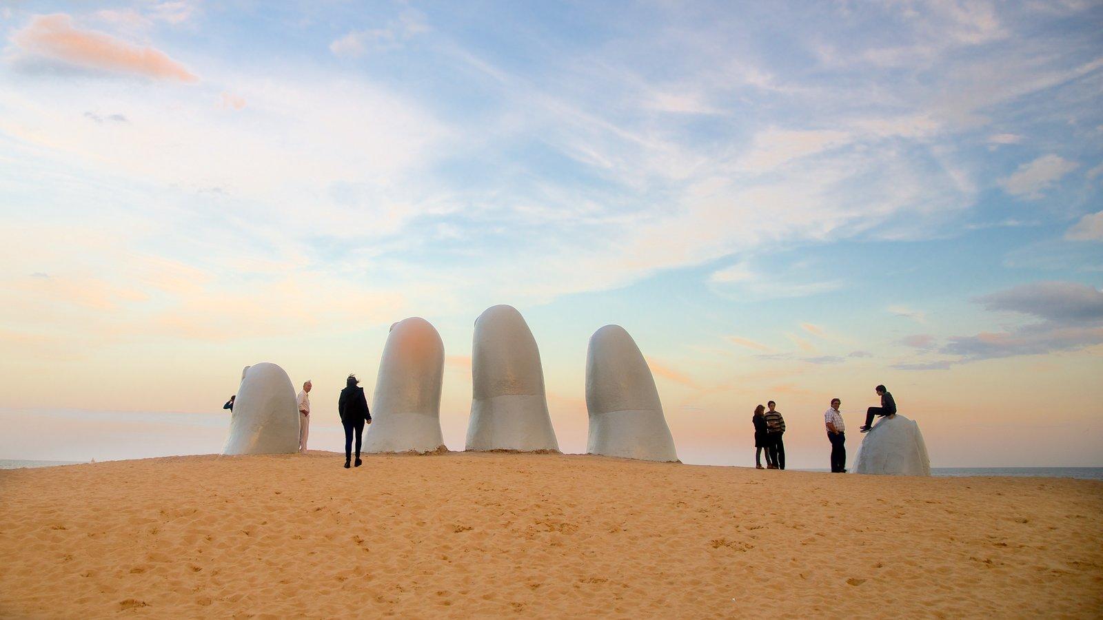Playa Brava caracterizando um pôr do sol, paisagens litorâneas e uma estátua ou escultura