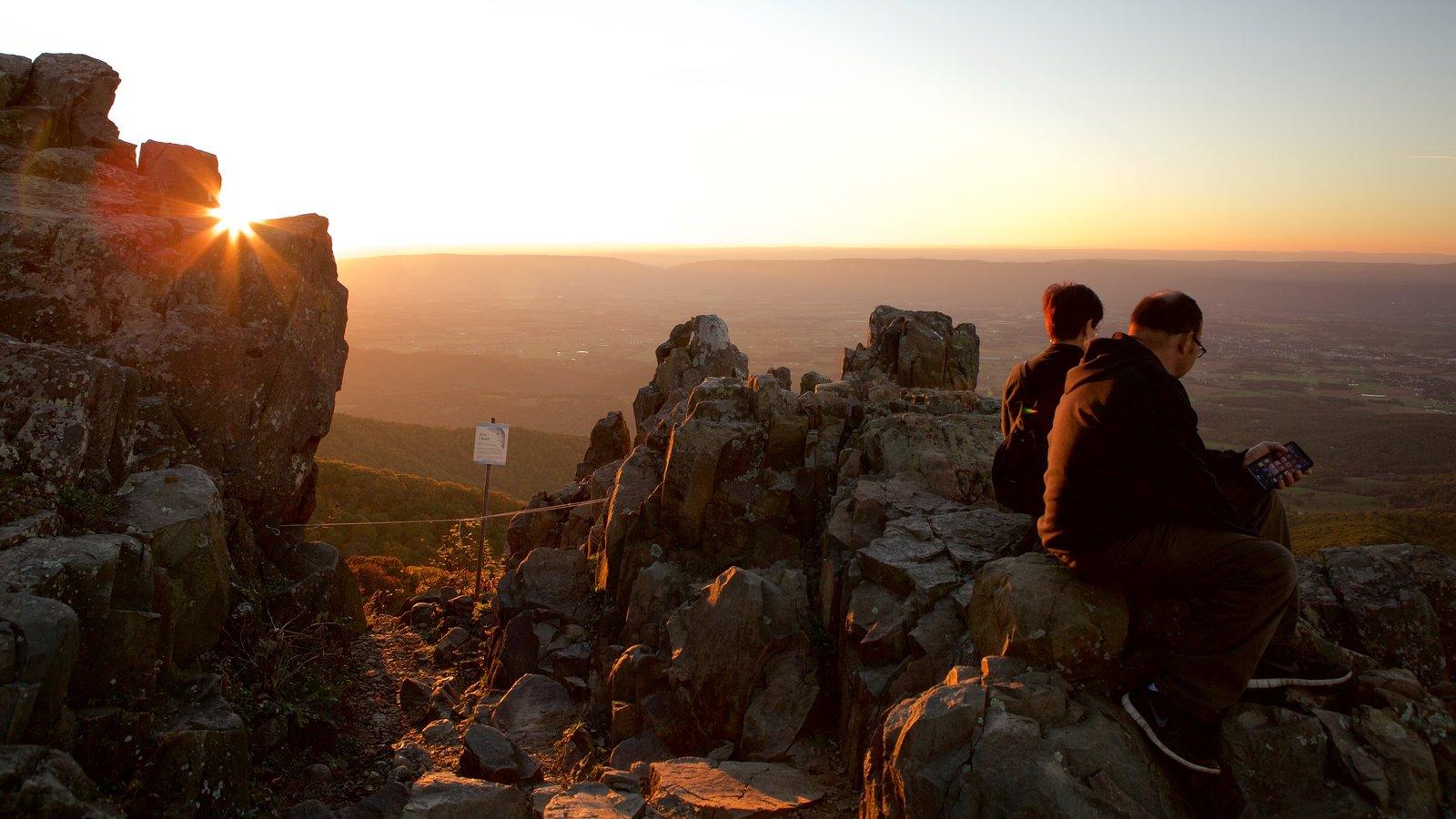 Parque Nacional Shenandoah que incluye montañas y una puesta de sol y también una pareja