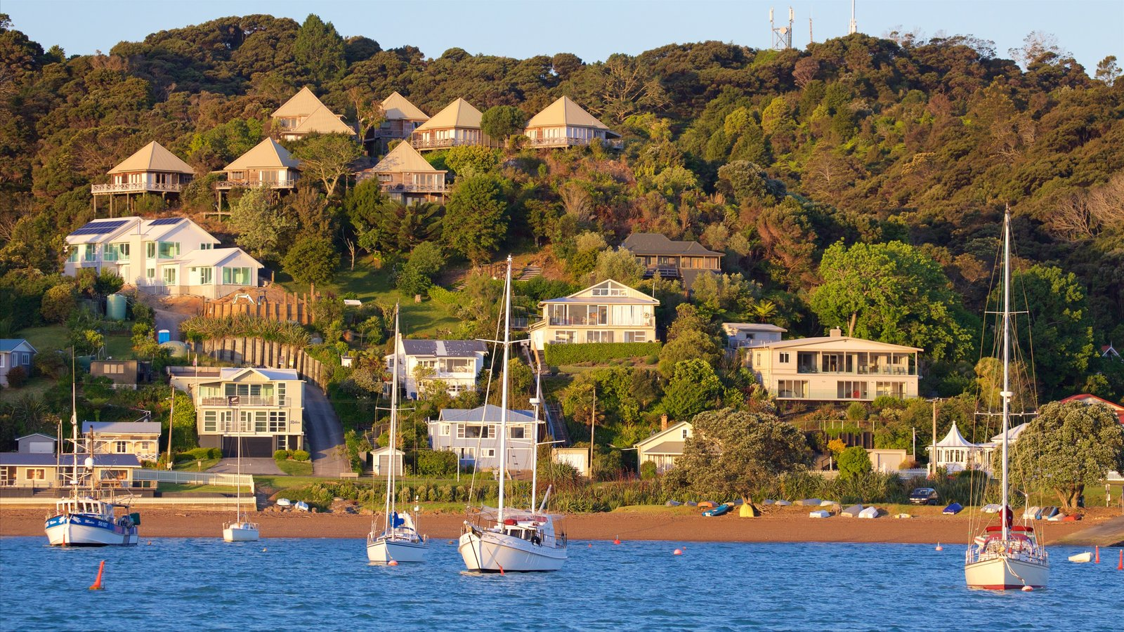 Russell which includes a coastal town, a sandy beach and a bay or harbor
