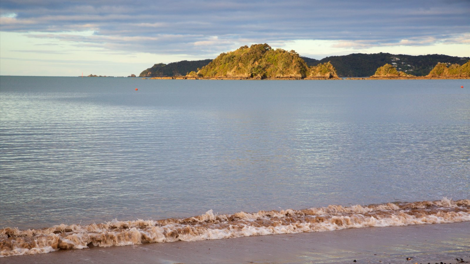 Paihia Beach which includes a bay or harbor, rocky coastline and a beach