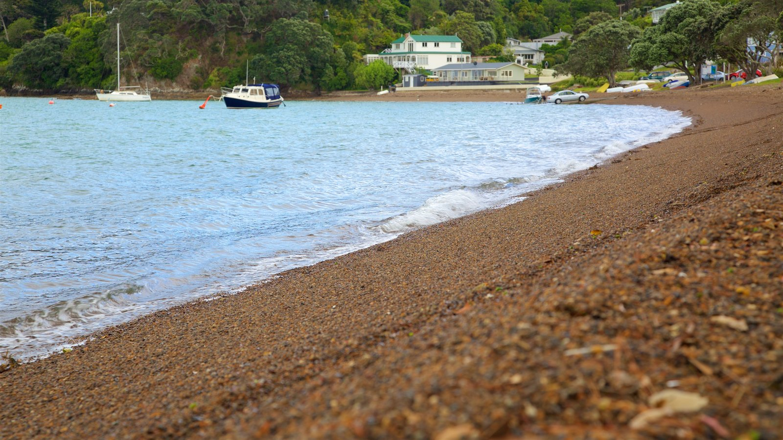 Russell Beach which includes a bay or harbor, a coastal town and a pebble beach