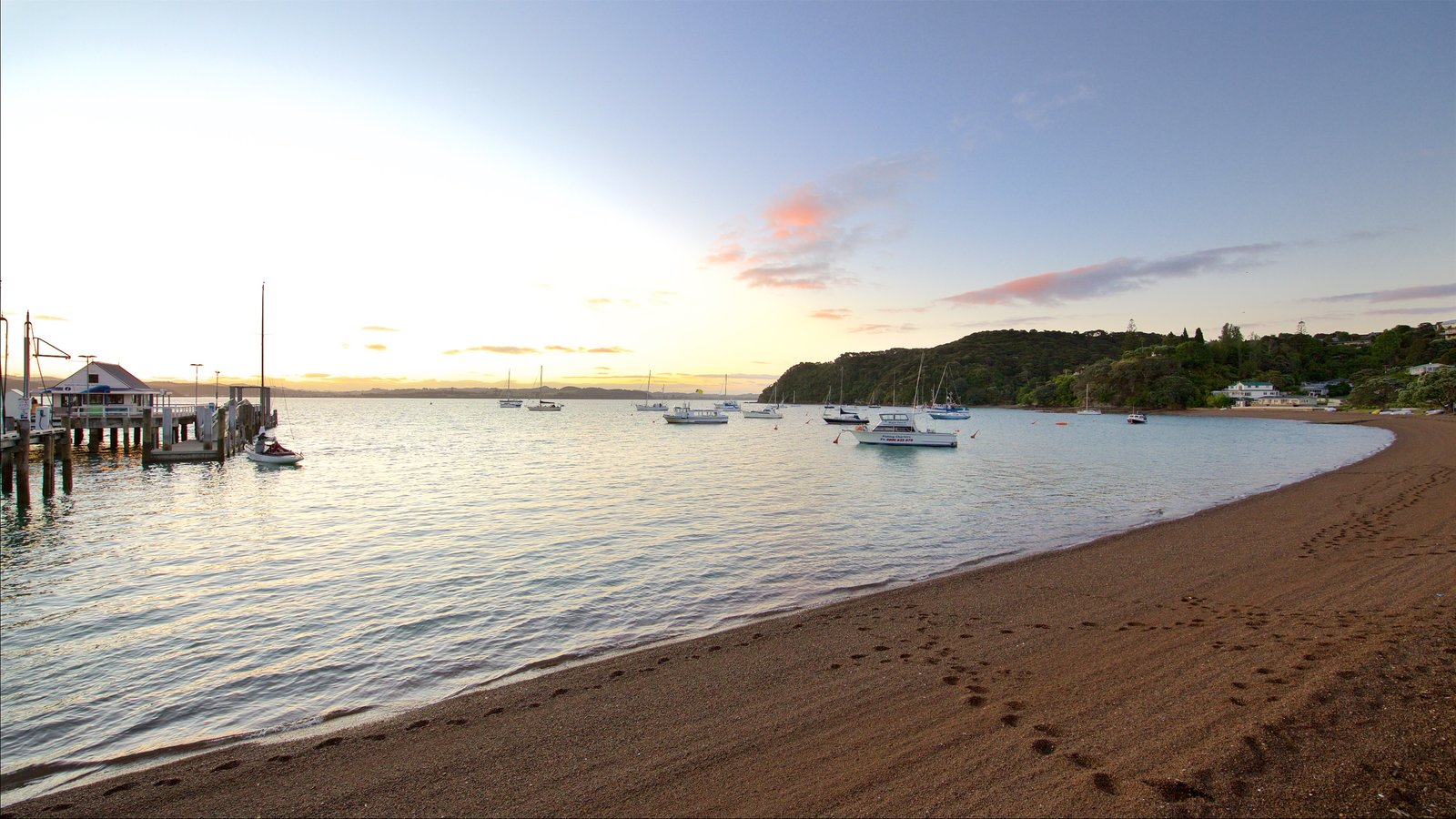 Russell Beach which includes a pebble beach, a bay or harbor and a sunset