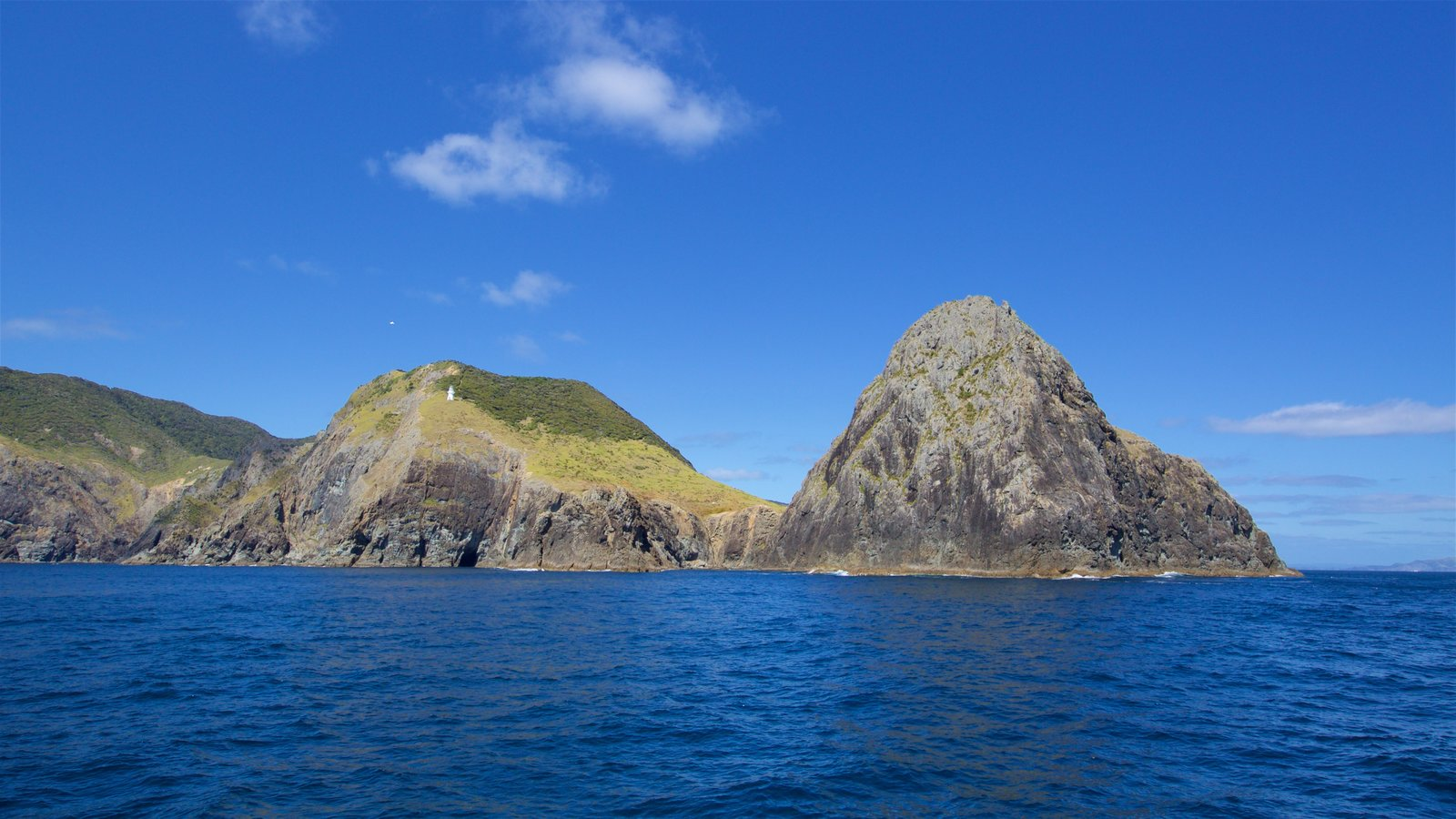 Cape Brett Lighthouse featuring rocky coastline and a bay or harbor