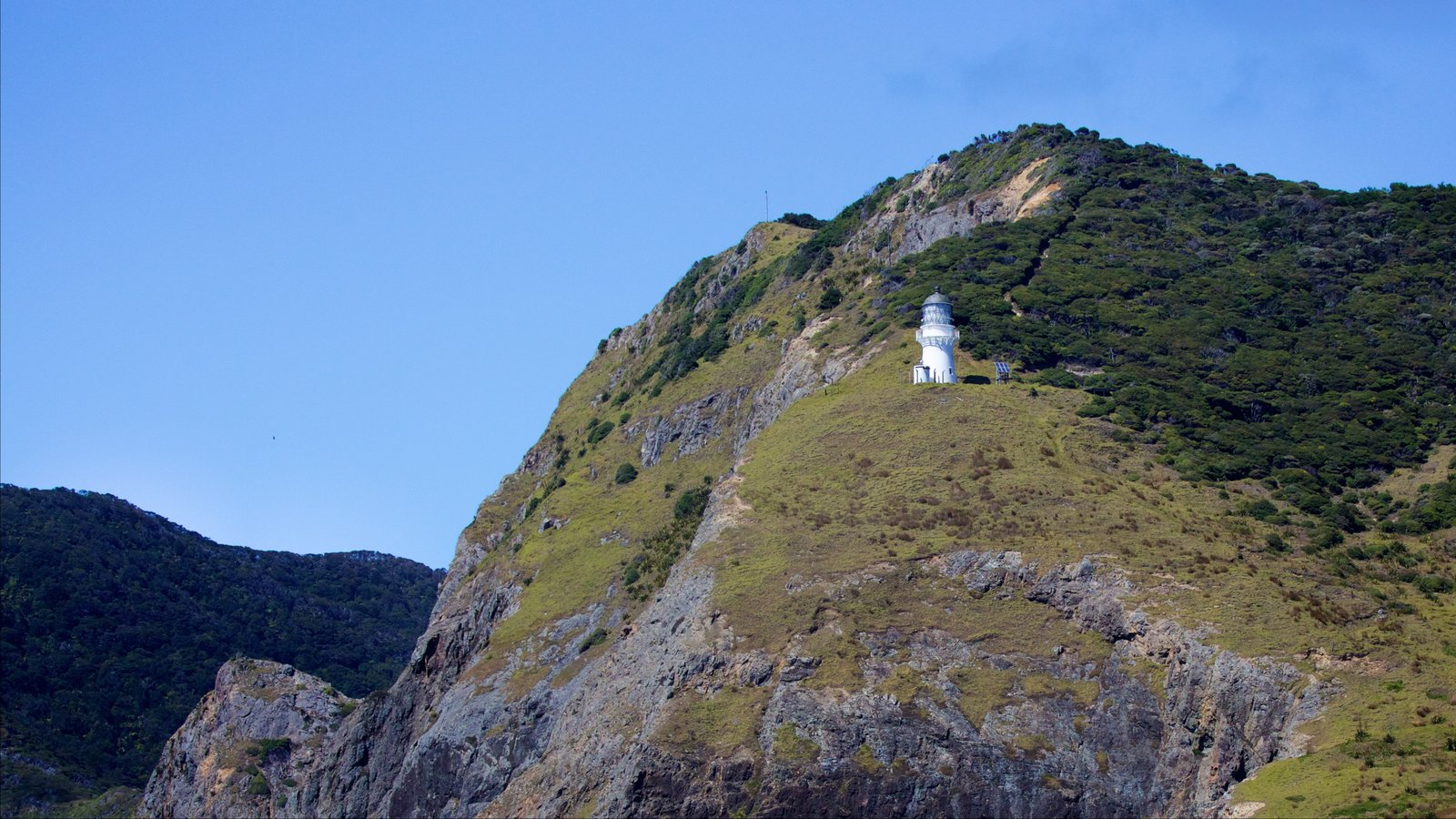 Cape Brett Lighthouse ofreciendo un faro y costa escarpada
