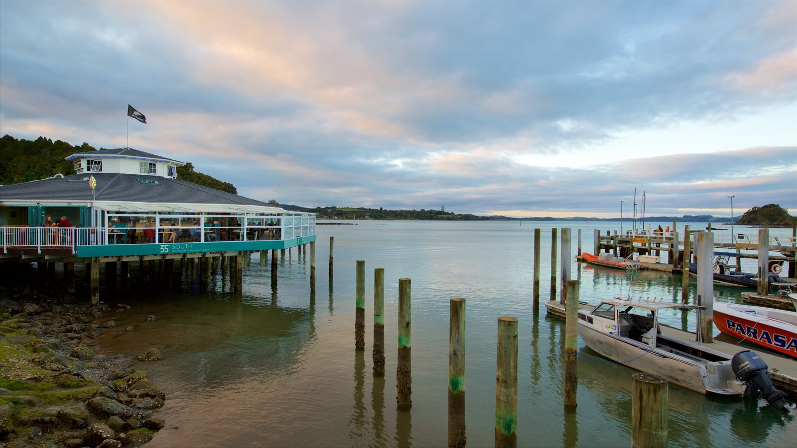 Paihia Wharf which includes a bay or harbor, a marina and a sunset