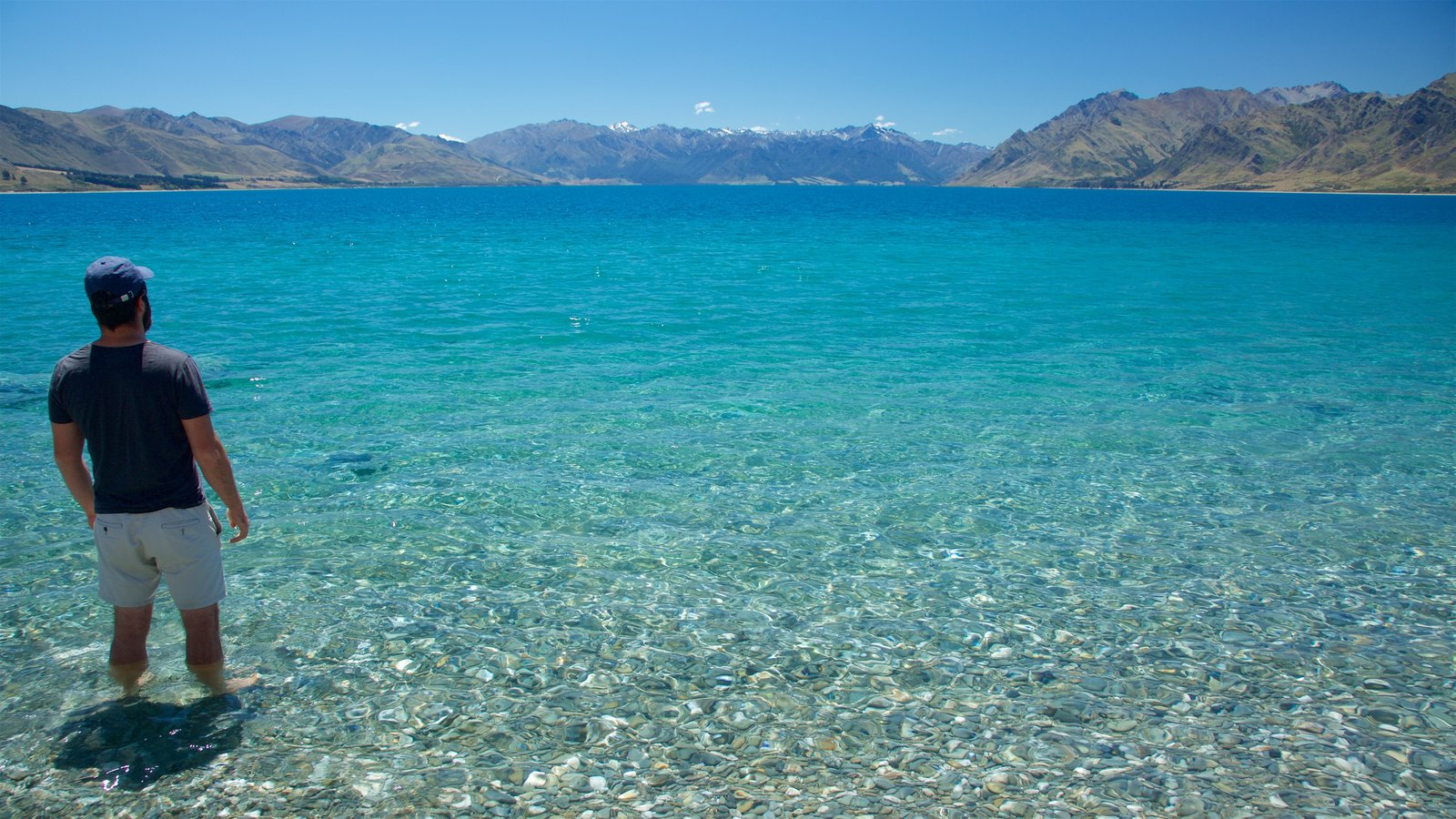 Lake Hawea showing a lake or waterhole, a pebble beach and mountains