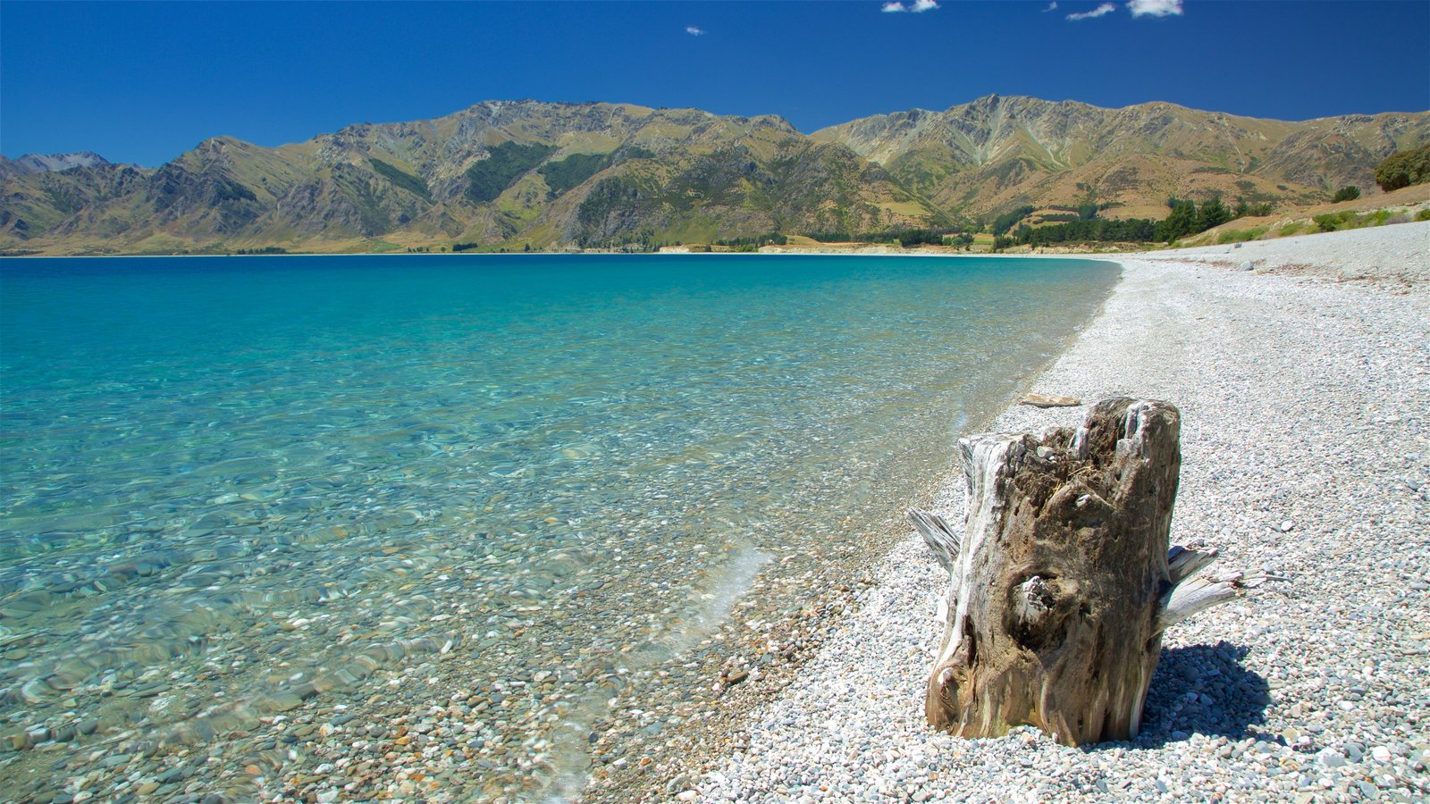 Lake Hawea showing mountains, a lake or waterhole and a pebble beach
