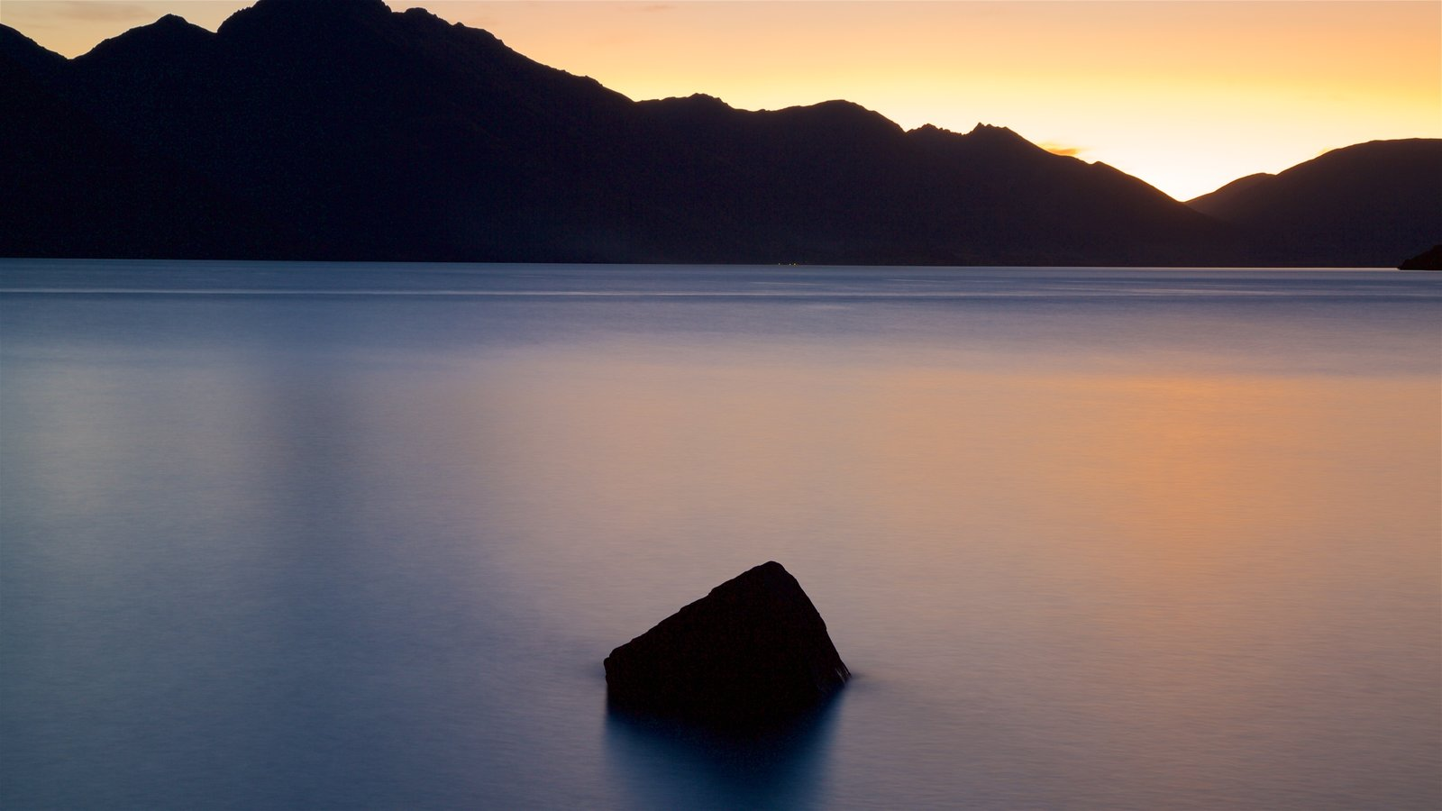 Lake Wakatipu which includes a lake or waterhole, a sunset and mountains