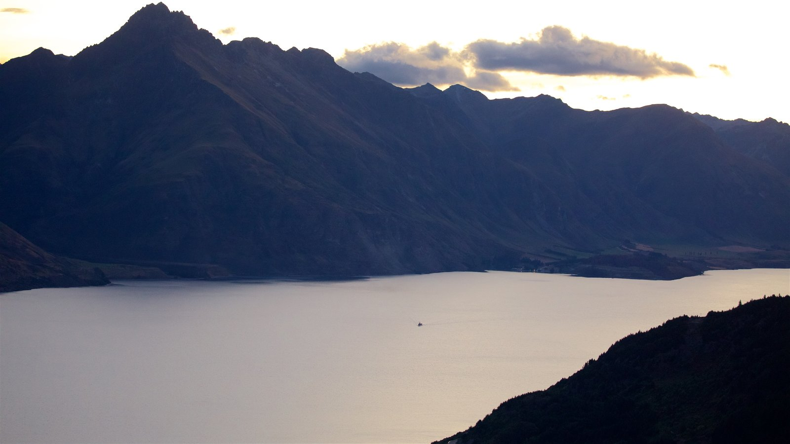 Sunshine Bay featuring a sunset, mountains and a lake or waterhole
