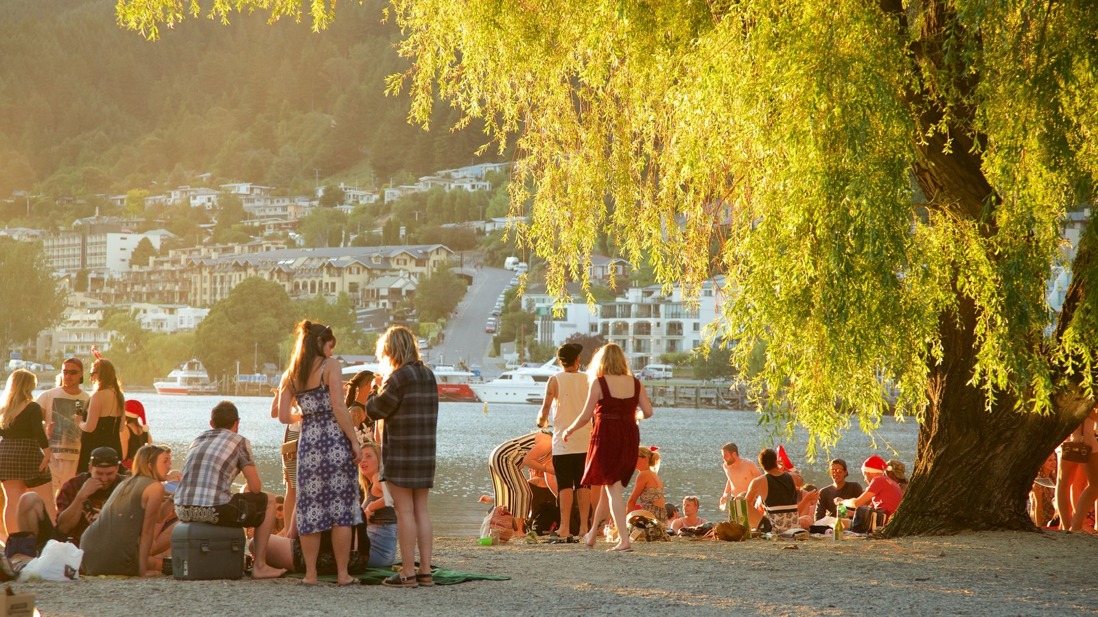 Queenstown Beach showing a pebble beach, a sunset and a small town or village