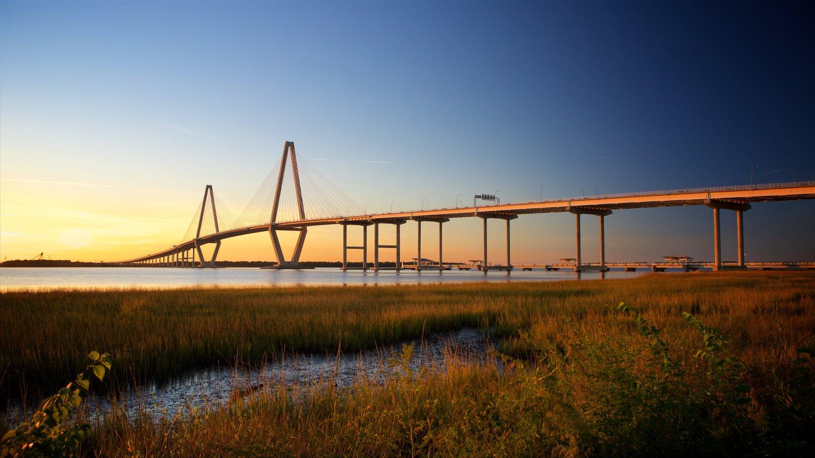 Arthur Ravenel Jr. Bridge que inclui uma ponte, um pôr do sol e pântano