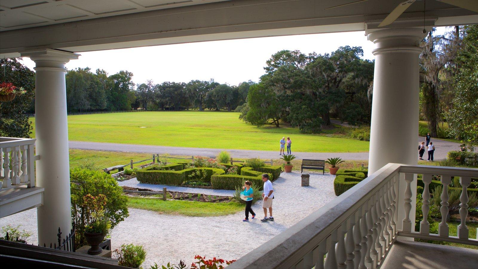 Magnolia Plantation and Gardens mostrando elementos de patrimônio e um jardim assim como um casal