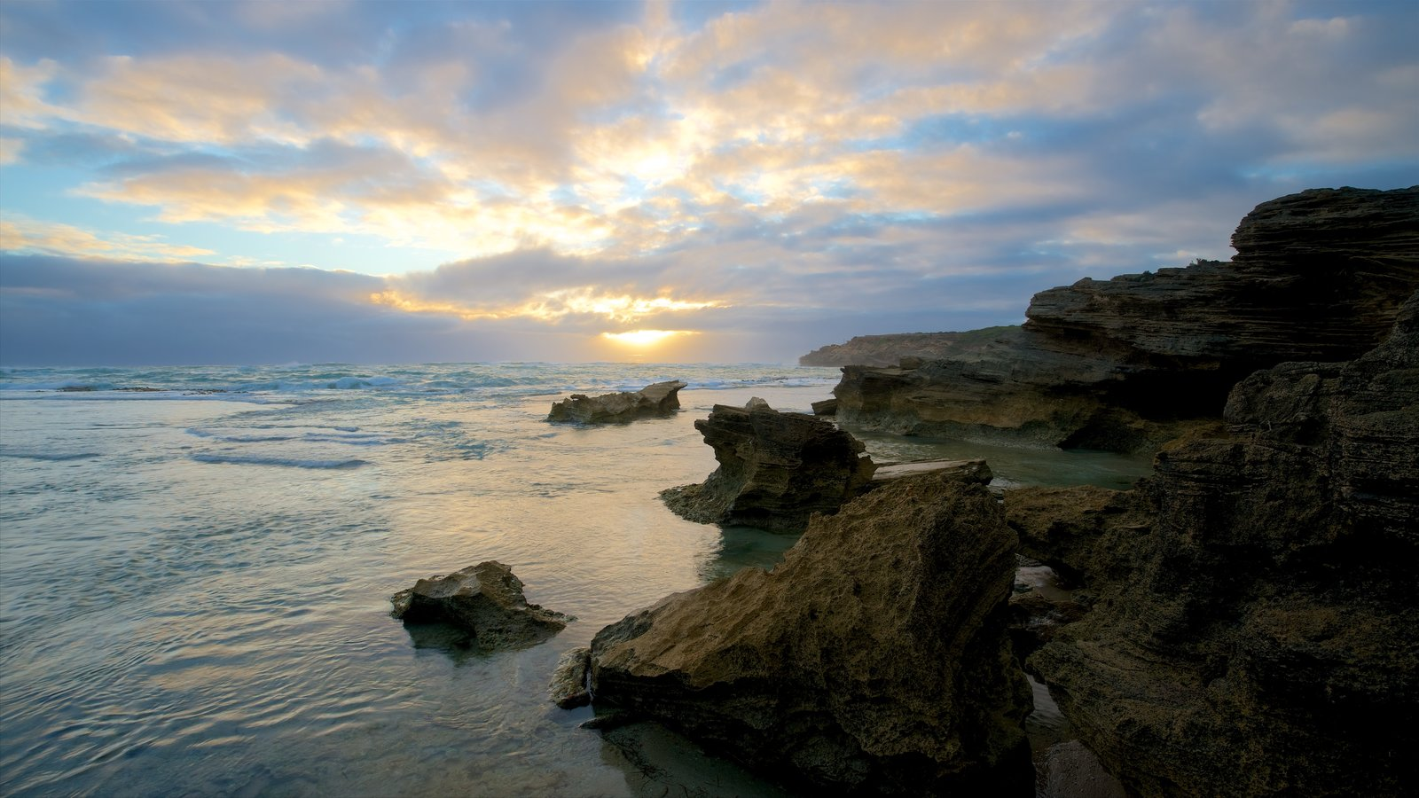 Warrnambool which includes a bay or harbor, a sunset and rugged coastline