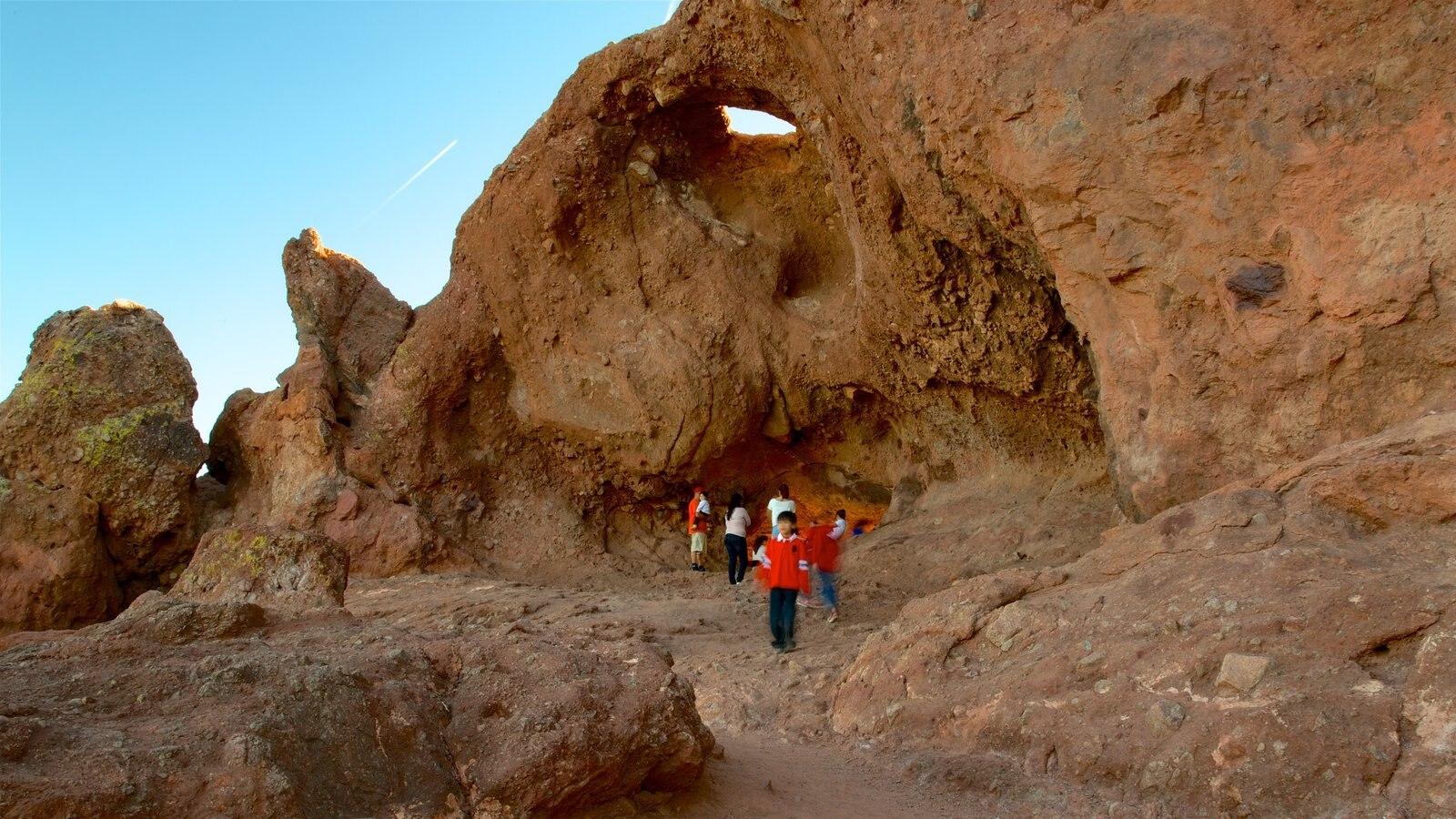 Hole in the Rock que inclui cenas tranquilas e um desfiladeiro ou canyon assim como um pequeno grupo de pessoas