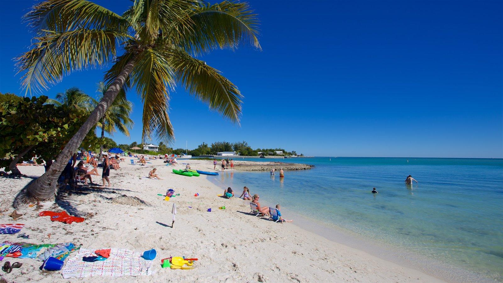 Sombrero Beach que inclui uma baía ou porto e uma praia de areia assim como um pequeno grupo de pessoas