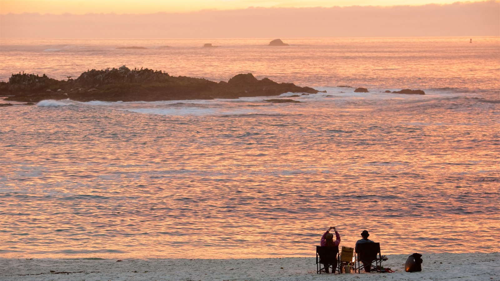 17-Mile Drive showing a sandy beach and a sunset as well as a couple