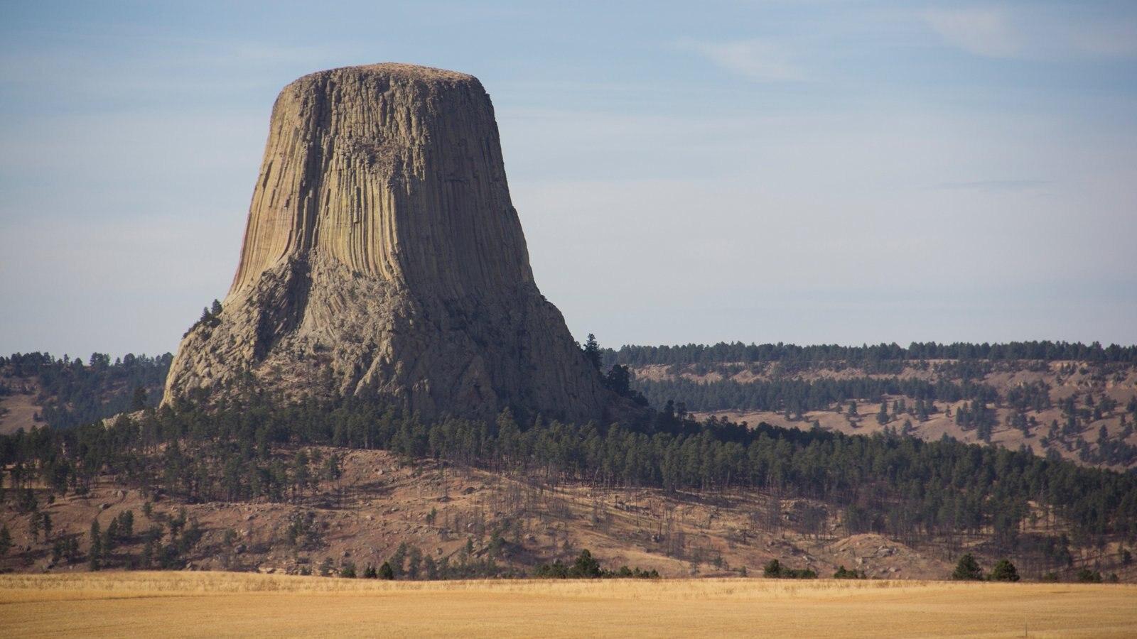 Devils Tower National Monument que inclui montanhas, cenas tranquilas e um pôr do sol