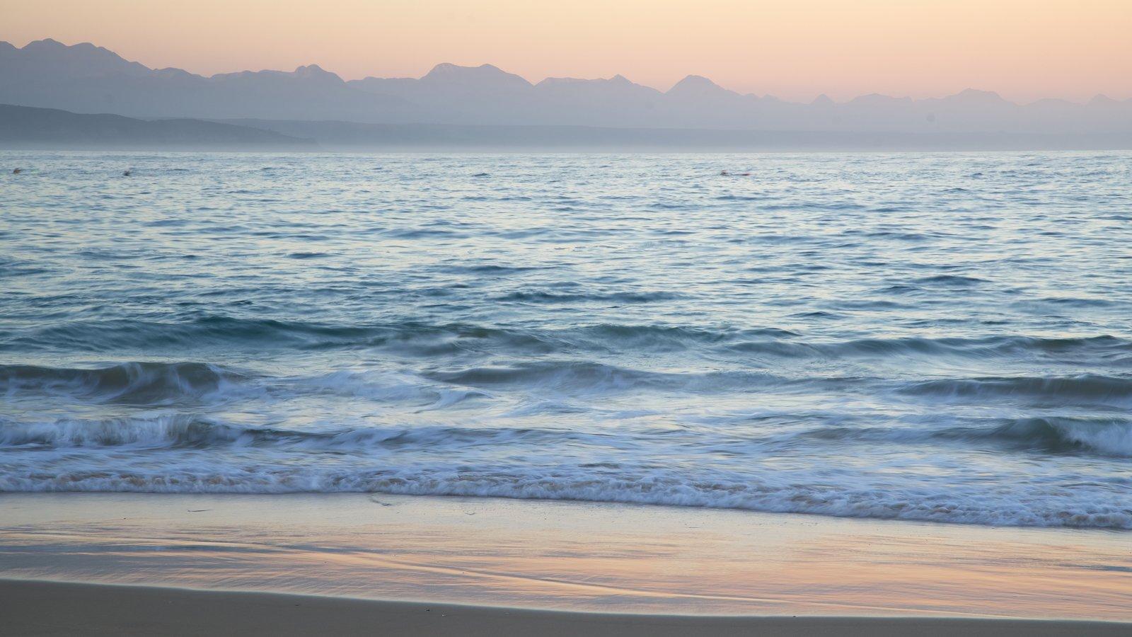 Playa de Plettenberg Bay ofreciendo una puesta de sol, una playa de arena y olas