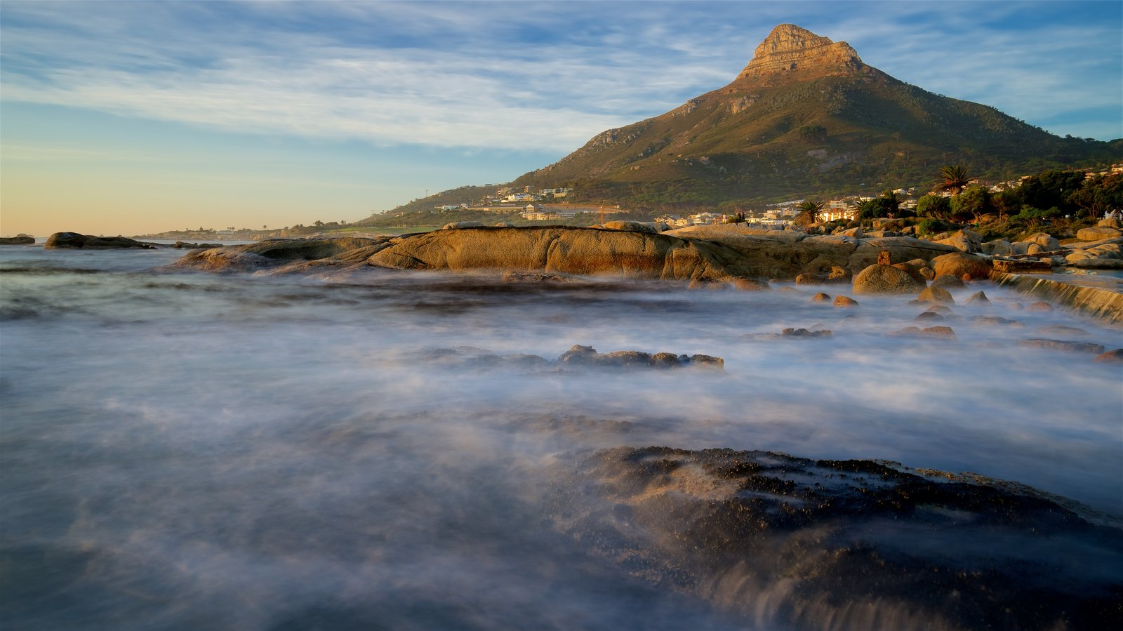 Camps Bay Beach showing waves and rocky coastline