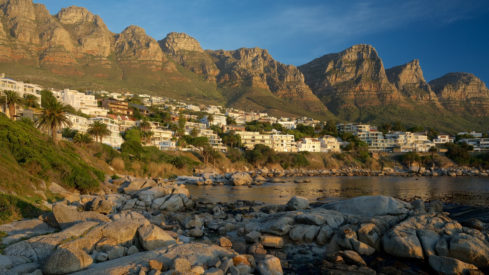 Camps Bay Beach which includes rugged coastline and a coastal town