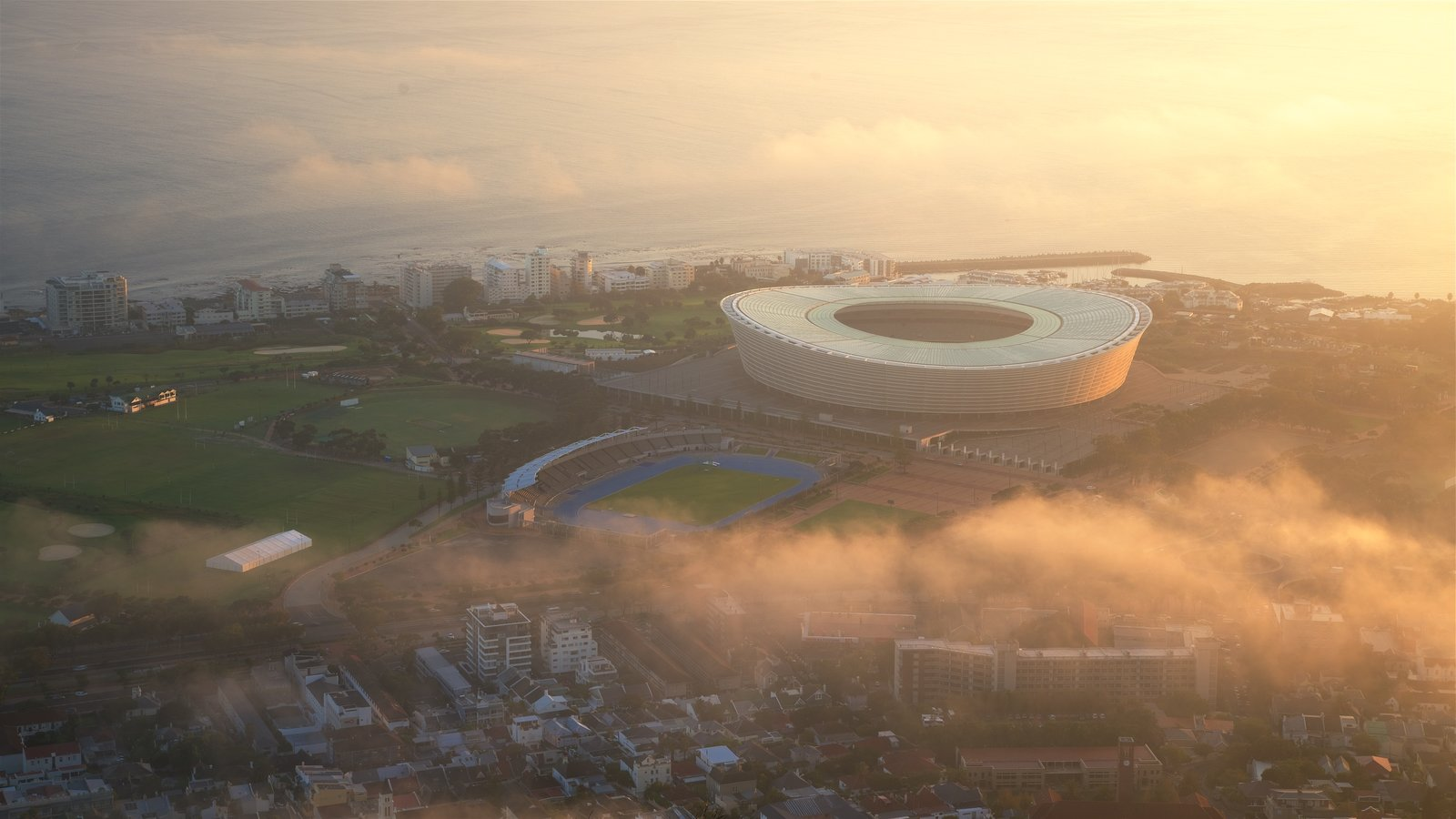 Cape Town Stadium which includes a sunset and a city